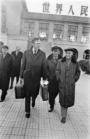 Balancing his carry-on bags, George H.W. Bush bids a final farewell at Beijing Airport in China, as he is about to depart for Washington, D.C., Dec. 7, 1975. Bush, former chief of U.S. Liaison mission in Beijing, was nominated to head the CIA in the U.S.