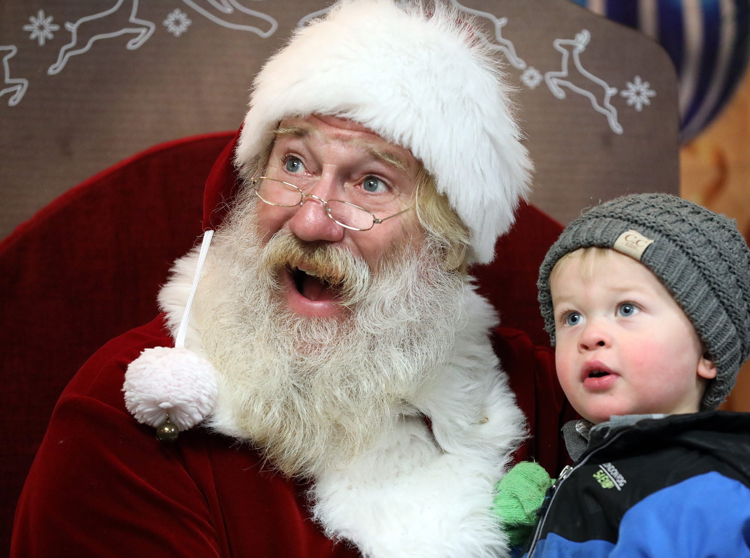Santa and Charlie McPherren, 2, of Van Meter smile as his parent takes a picture during UCAN's third annual Light Up Urbandale on Sunday, Dec. 2, 2018 at Lions Park in Urbandale. Holiday festivities included a visit from Santa, crafts, goodies, official tree lighting ceremony, live reindeer and entertainment. This event helps raise awareness and support for the Urbandale Community Action Network Holiday Helping Hands Programs for families, kids, teens and seniors in need.