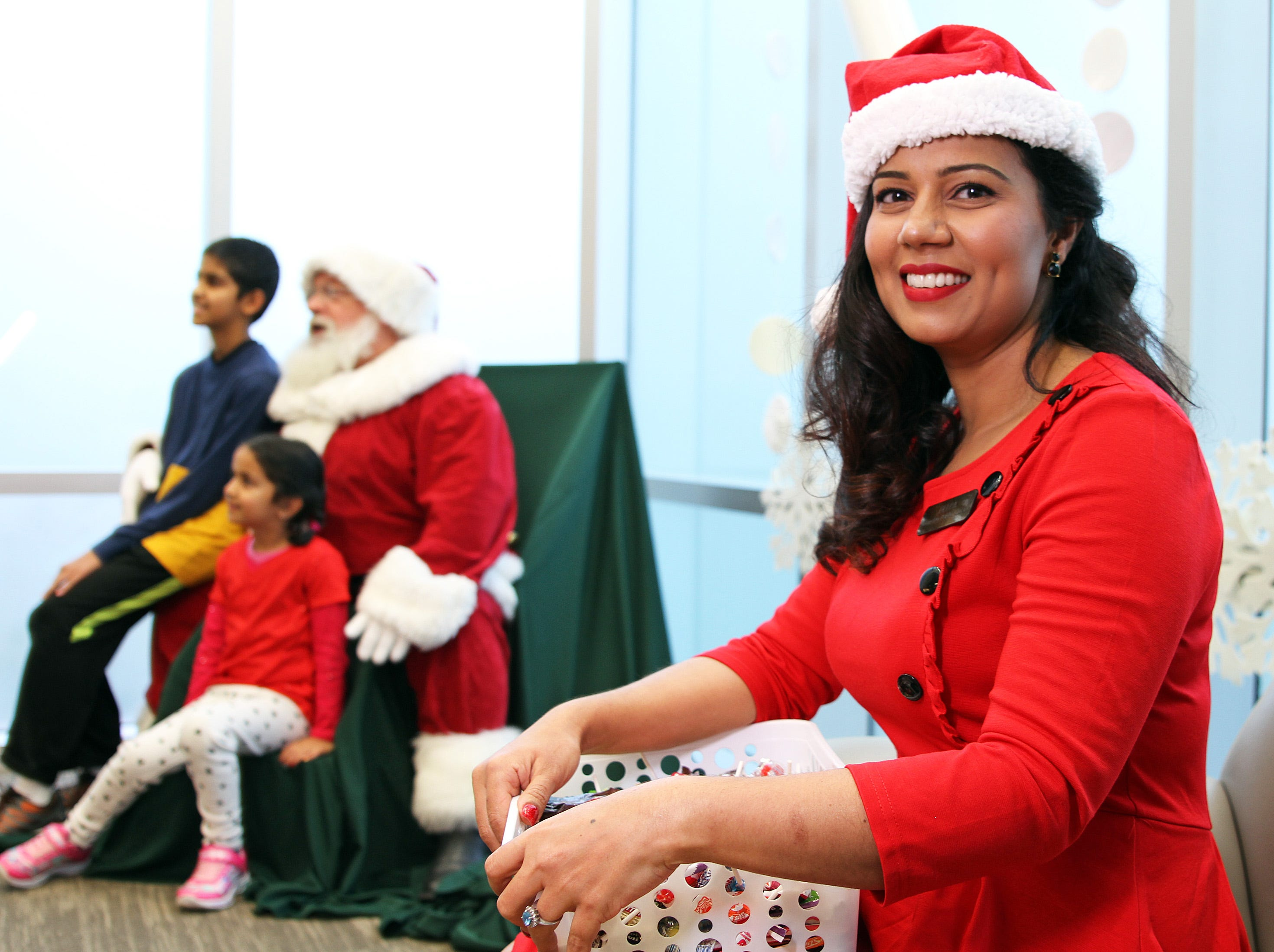 Library Associate Deepa Swaroop helps Santa hand out candy to the kids after their visit during Holidays in Johnston on Saturday, Dec. 1, 2018 at the Johnston Public Library featuring a gingerbread house contest, cookie decorating, holiday music performed by the Johnston Middle School Ninth Grade Chamber Choir, story time and Santa.