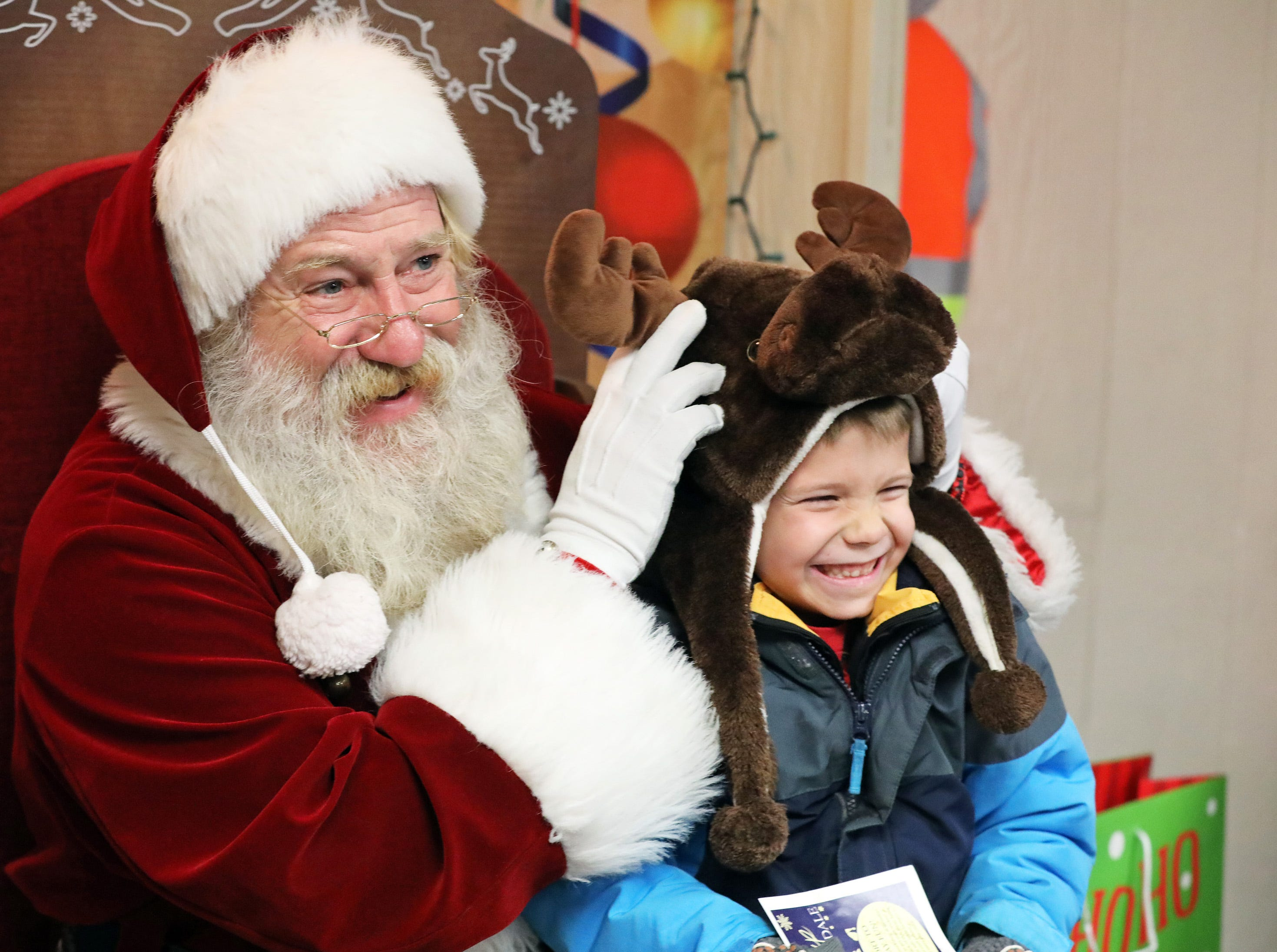 Santa playfully adjusts the moose hat of Jeff Neas, 6, of Urbandale during UCAN's  third annual Light Up Urbandale on Sunday, Dec. 2, 2018 at Lions Park in Urbandale. Holiday festivities included a visit from Santa, crafts, goodies, official tree lighting ceremony, live reindeer and entertainment.