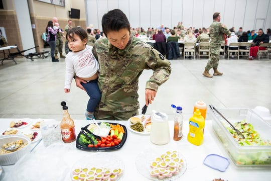 2nd Lt. Trang Jorgensen, the Iowa National Guard's first and only female officer in the infantry, fills a plate with food while she holds her 18-month-old daughter, Eveleen Rae, on her hip during a family day pot-luck on Sunday, Dec. 2, 2018, at Camp Dodge.
