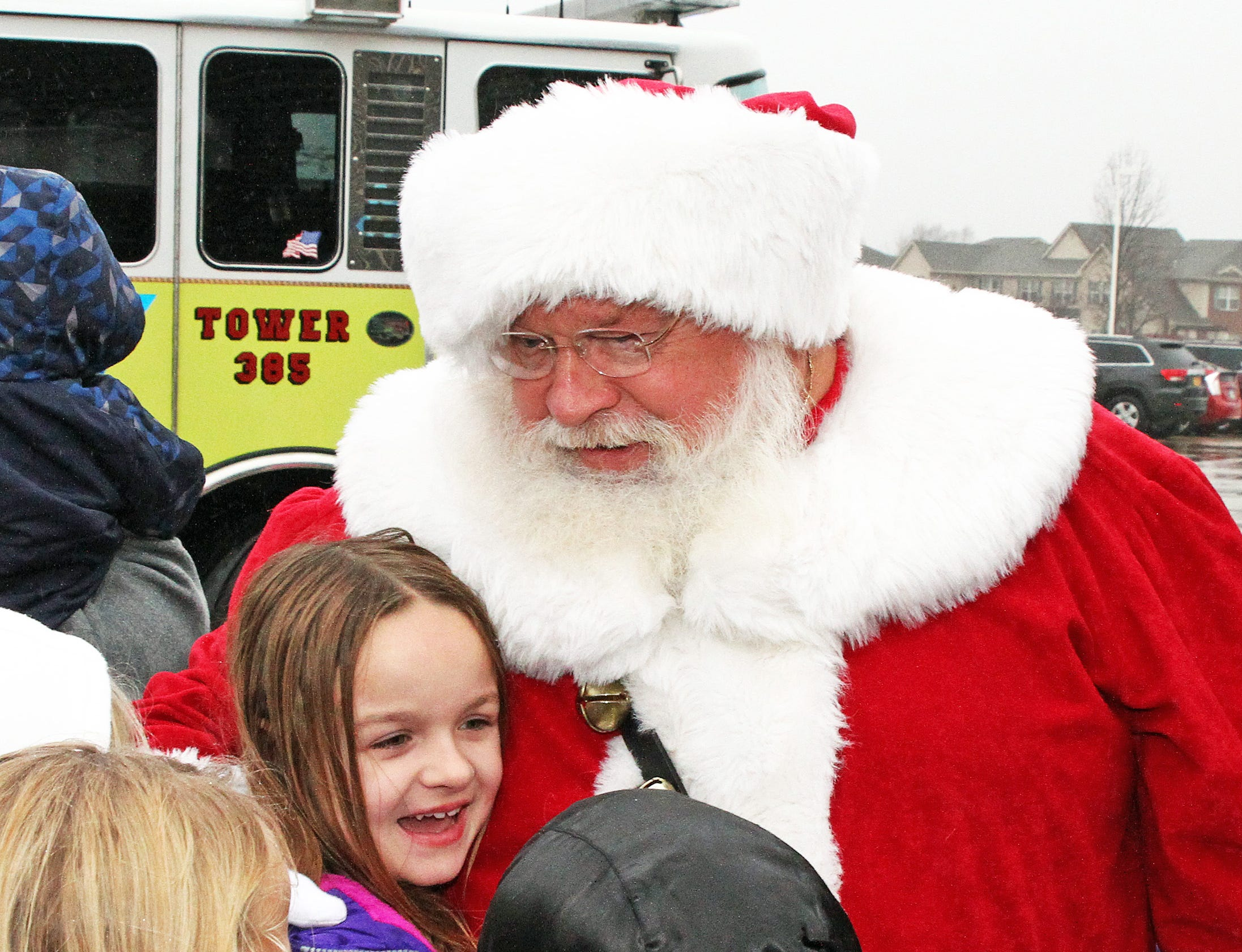 Santa greets the children as he arrives by fire truck during Holidays in Johnston on Saturday, Dec. 1, 2018 at the Johnston Public Library featuring a gingerbread house contest, cookie decorating, holiday music performed by the Johnston Middle School Ninth Grade Chamber Choir and story and craft time.