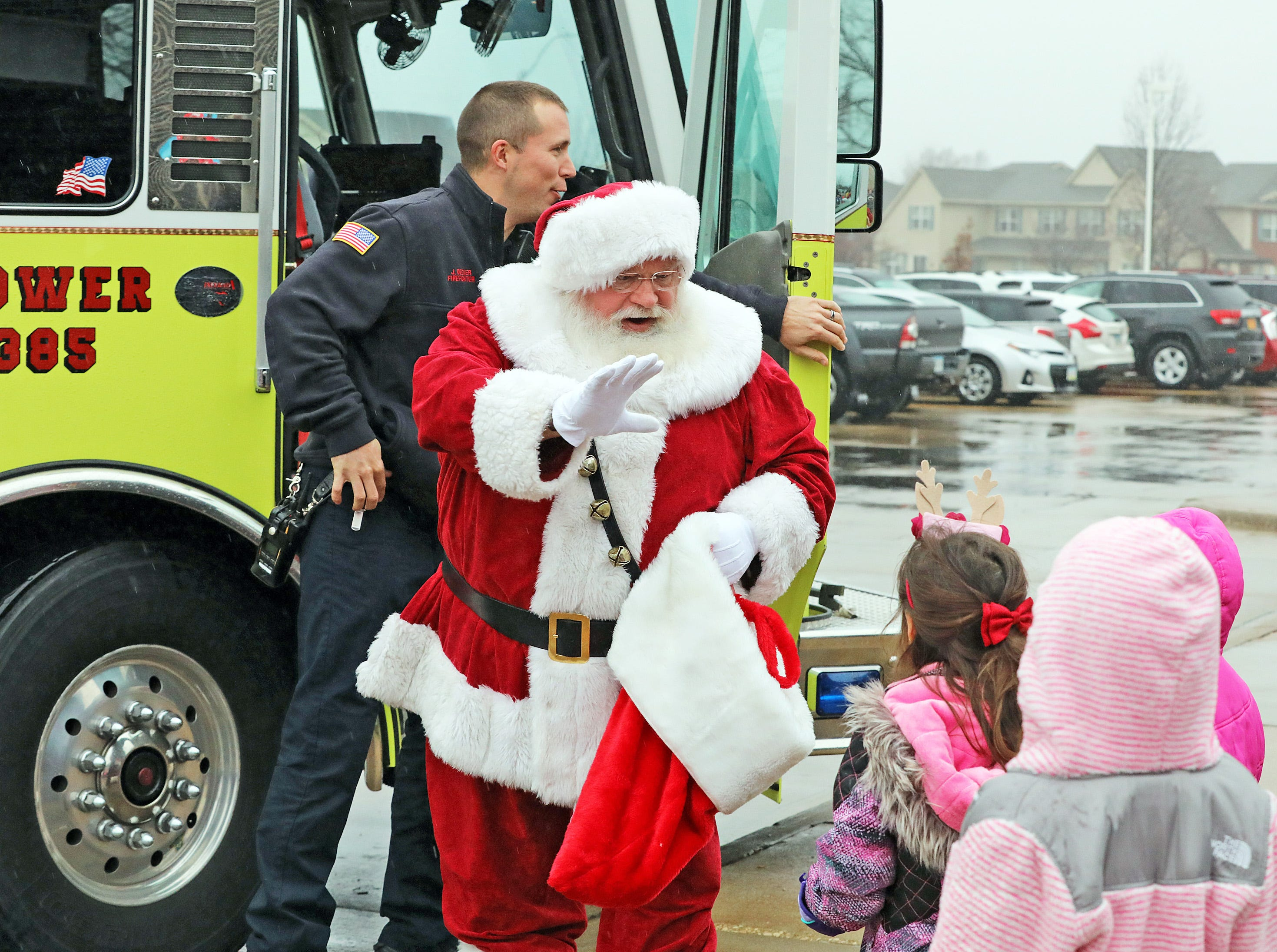 Santa greets the children as he arrives by fire truck during Holidays in Johnston on Saturday, Dec. 1, 2018 at the Johnston Public Library featuring a gingerbread house contest, cookie decorating, holiday music performed by the Johnston Middle School Ninth Grade Chamber Choir, story time and Santa.