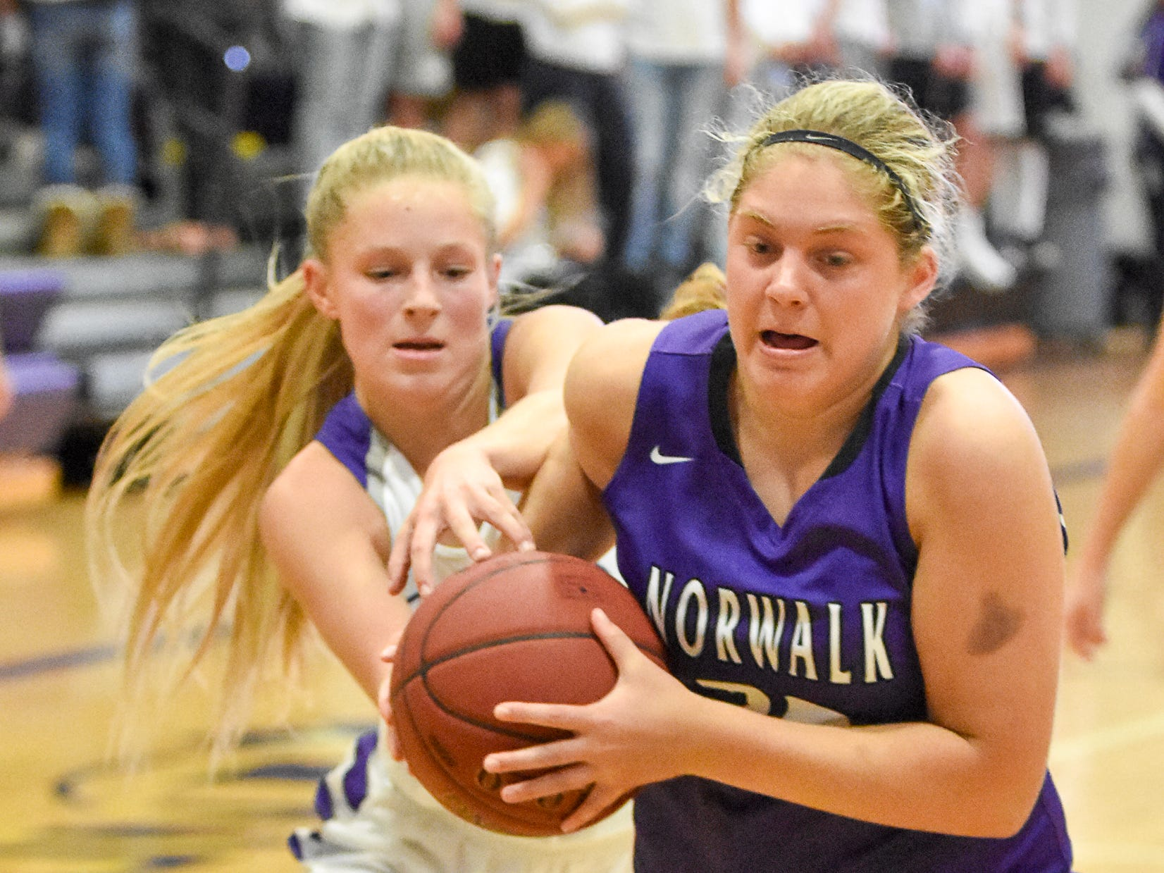 Norwalk's Emma Soukup fends off Indianola's Allison Coffey during the game. The Indianola girls' basketball team picked up their first win of the season with a 57-34 home victory over Norwalk on Nov. 30, 2018.