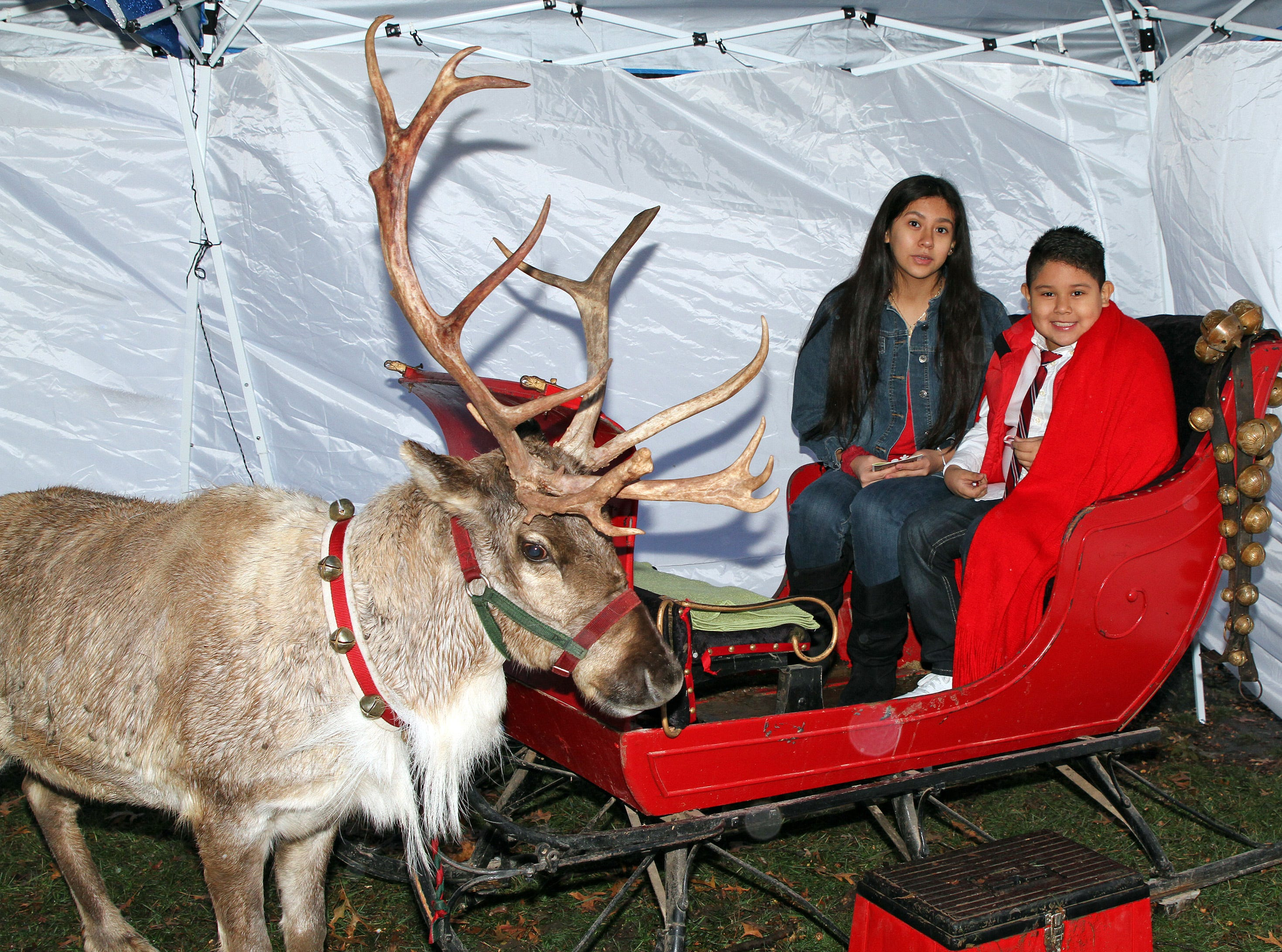 Woody the Reindeer stops for a photo with Alonda, 16, and Steven Luna, 8, of Urbandale during UCAN's third annual Light Up Urbandale on Sunday, Dec. 2, 2018 at Lions Park in Urbandale.