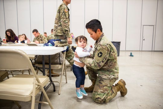 2nd Lt. Trang Jorgensen, the Iowa National Guard's first and only female officer in the infantry, sets down her 18-month-old daughter, Eveleen Rae, during a family day pot-luck on​ Sunday, Dec. 2, 2018, at Camp Dodge in Johnston, Iowa.