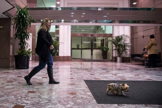 Jeannie Floer, an occupancy planner for Ford Land, takes her dog Natasha out for a walk through the lobby in Fairlane Plaza South in Dearborn on Friday, Nov. 30, 2018.
