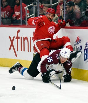 Detroit Red Wings center Luke Glendening falls atop of Colorado Avalanche right wing Mikko Rantanen during the first period in Detroit, Sunday, Dec. 2, 2018.