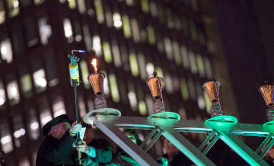 The first flame is lit at the annual lighting of the Hanukkah menorah by Chabad, at Campus Martius in Detroit on Sunday, Nov. 2, 2018 in Detroit.