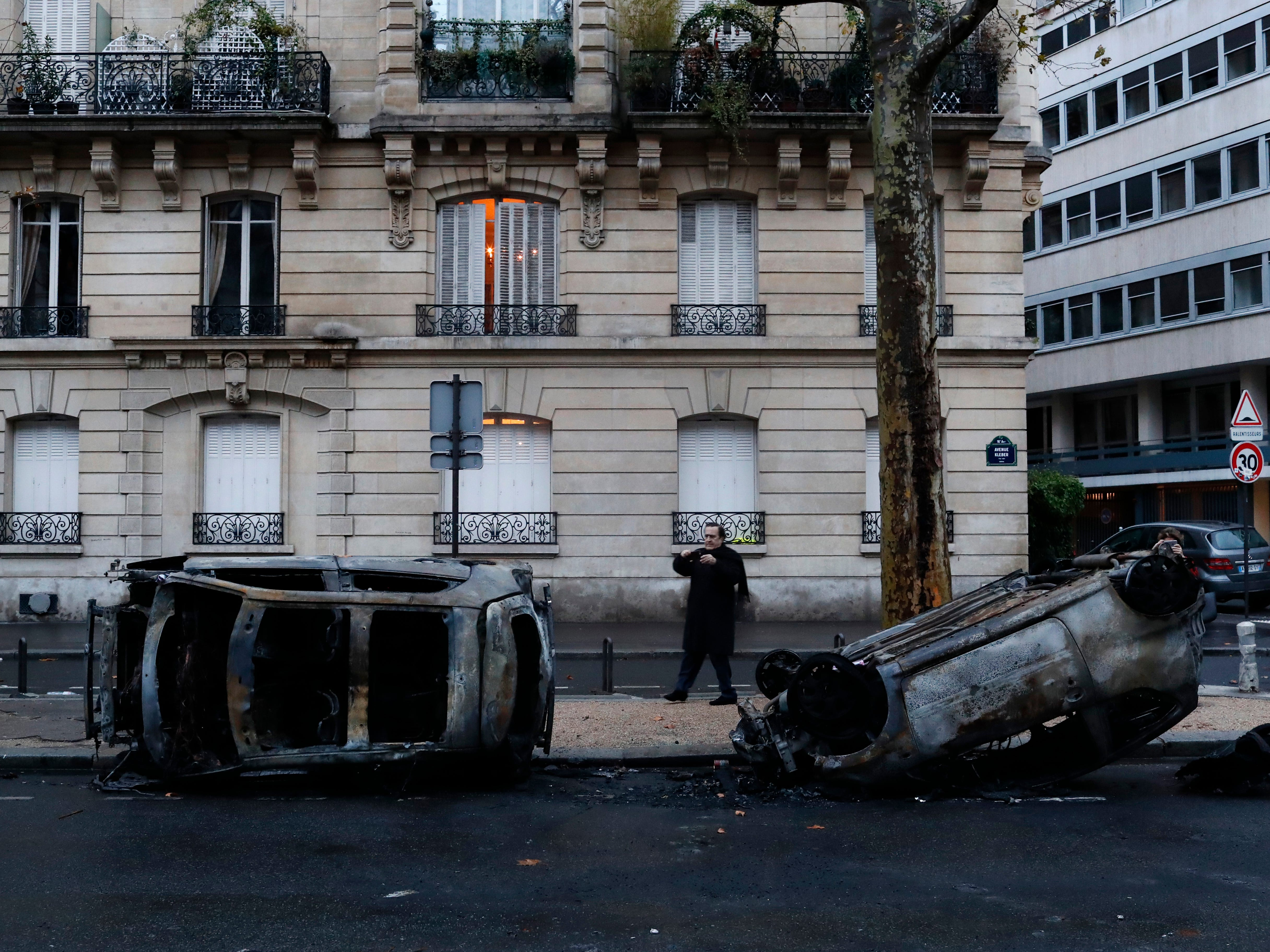 A man takes a snapshot of charred cars the day after a demonstration, near the Arc de Triomphe, in Paris, Sunday, Dec. 2, 2018. A protest against rising taxes and the high cost of living turned into a riot in the French capital, as activists torched cars, smashed windows, looted stores and tagged the Arc de Triomphe with multi-colored graffiti.