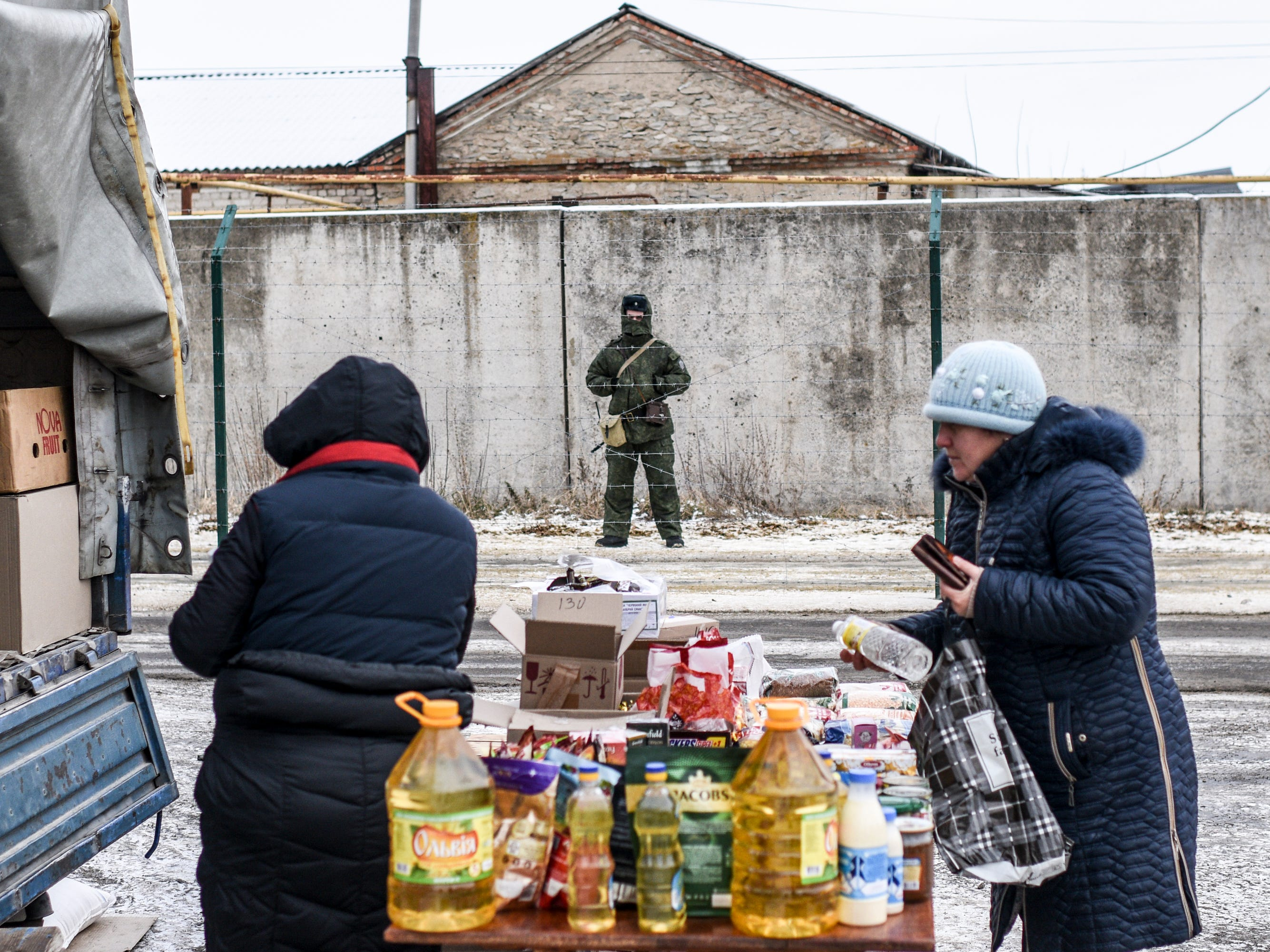 In this photo taken on Saturday, Dec. 1, 2018, A Russian border guard stands behind barbed wire on the Russian side of the Russia-Ukraine border as people buy and sell at Saturday's market in Milove, eastern Ukraine, one village, which is crossed by the main road called Friendship of People's Street and barbed wire. People on the streets easily mix both Russia and Ukrainian languages without making a political statement of it, but earlier this year, Russia built a barbed wire fence on the Friendship of People's street, marking the border with Ukraine in a metaphorical statement about the long-simmering conflict between the countries.