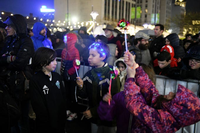 Harry Wessels, 8, blows a pinwheel with his friend, Liam Burk, 10, left, both of Grosse Pointe at the Menorah in the D celebration at Campus Martius in Detroit on Dec. 2, 2018. Holding up a pinwheel at right is Audrey Burk, 7. The eighth annual lighting of the menorah in downtown Detroit is done at the start of Hanukkah.