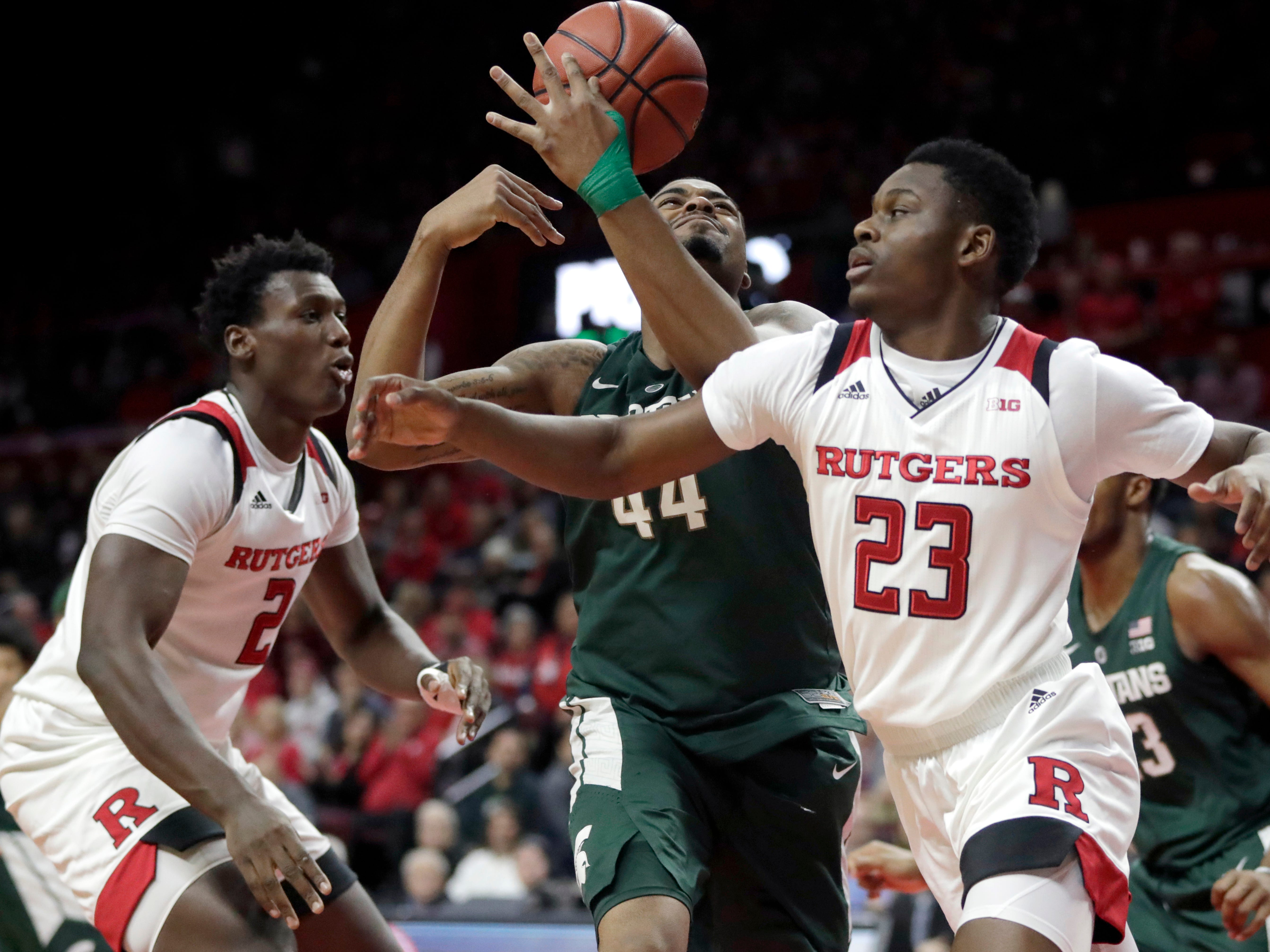 Michigan State forward Nick Ward (44) collects a rebound while Rutgers guard Montez Mathis (23) and center Shaquille Doorson (2) attack during the first half of an NCAA college basketball game, Friday, Nov. 30, 2018, in Piscataway, N.J. (AP Photo/Julio Cortez)