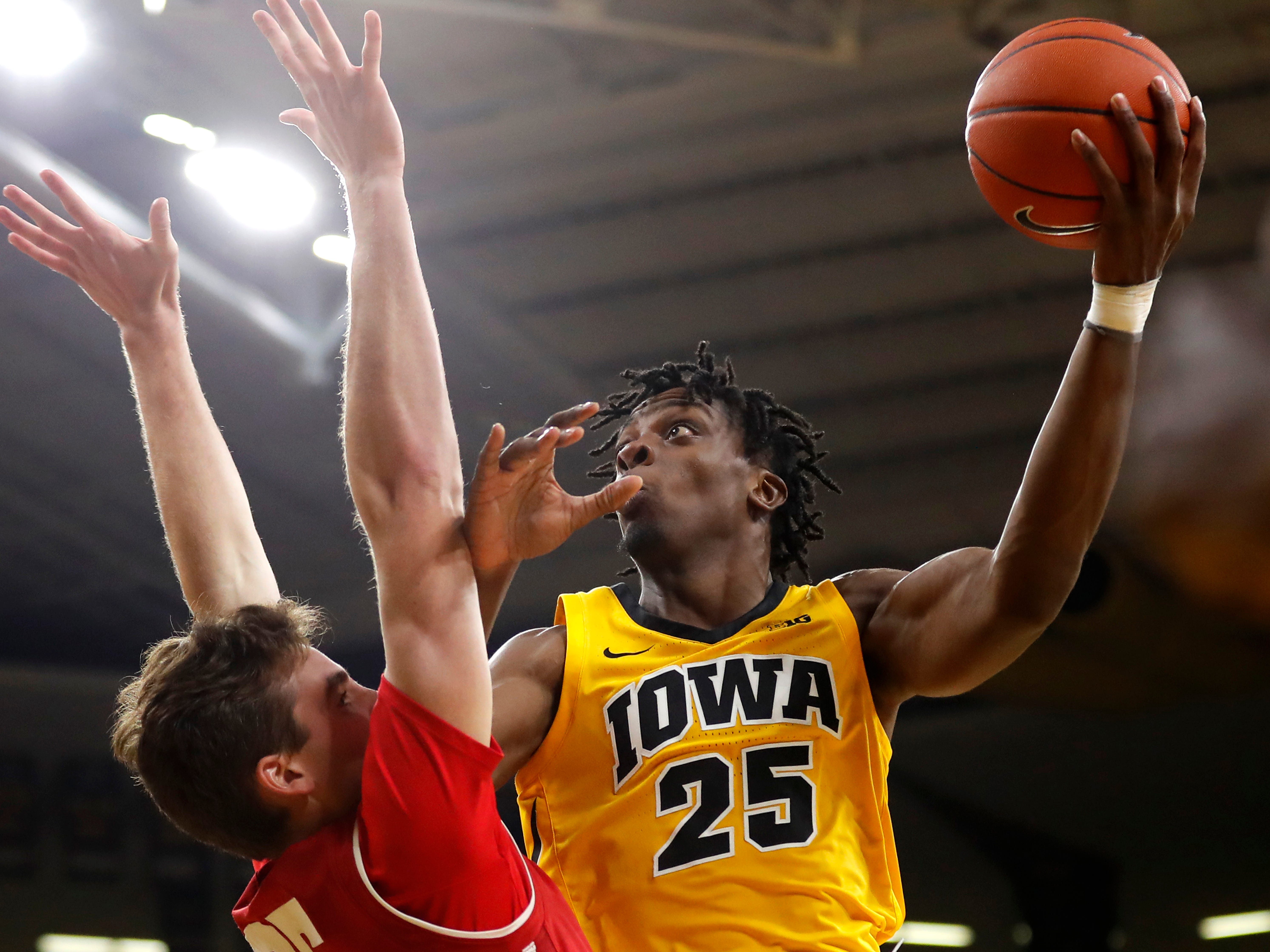 Iowa forward Tyler Cook (25) shoots over Wisconsin forward Nate Reuvers during the second half of an NCAA college basketball game Friday, Nov. 30, 2018, in Iowa City, Iowa. Wisconsin won 72-66. (AP Photo/Charlie Neibergall)