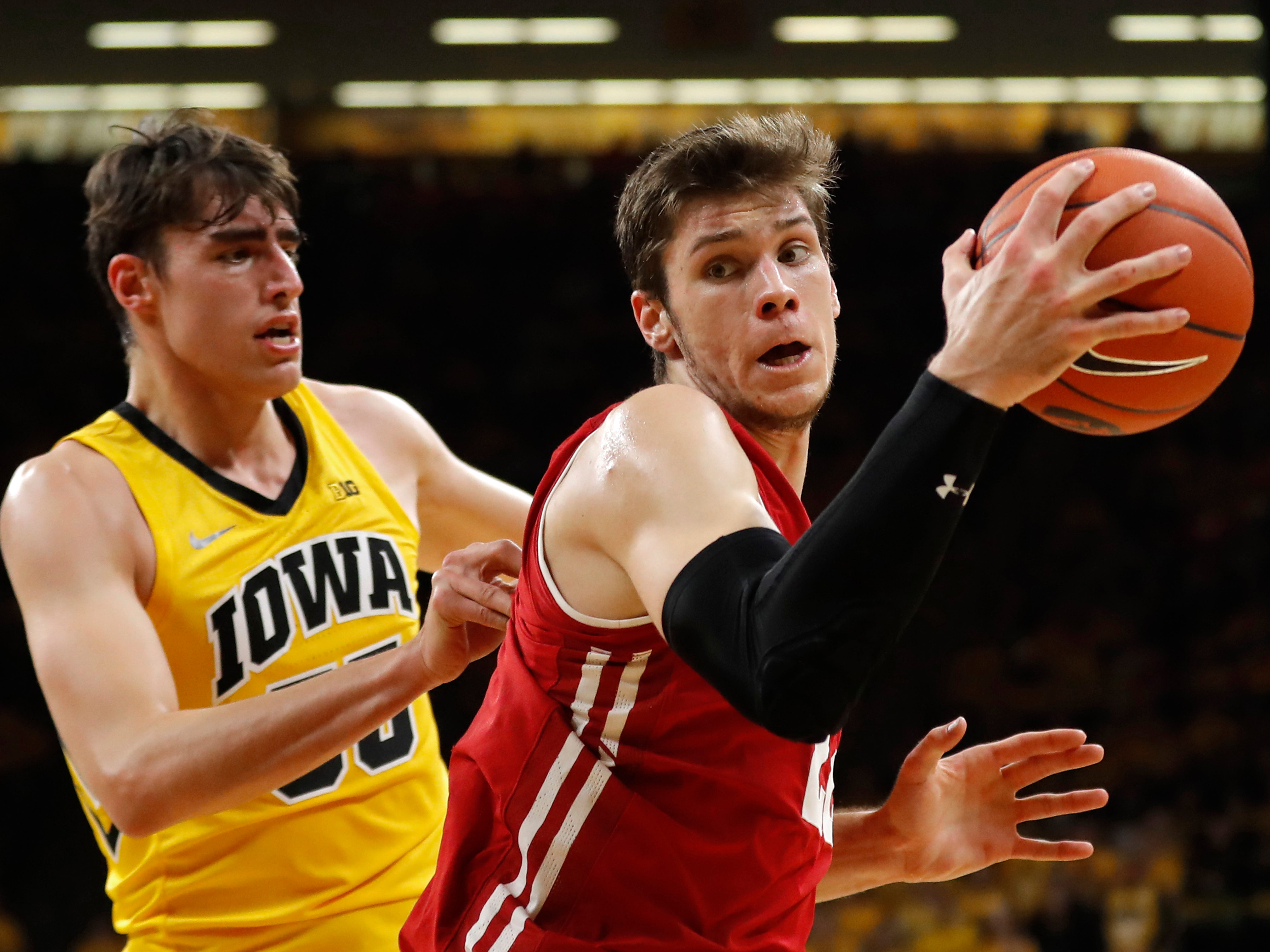 Wisconsin forward Ethan Happ drives past Iowa forward Luka Garza, left, during the first half of an NCAA college basketball game Friday, Nov. 30, 2018, in Iowa City, Iowa.(AP Photo/Charlie Neibergall)