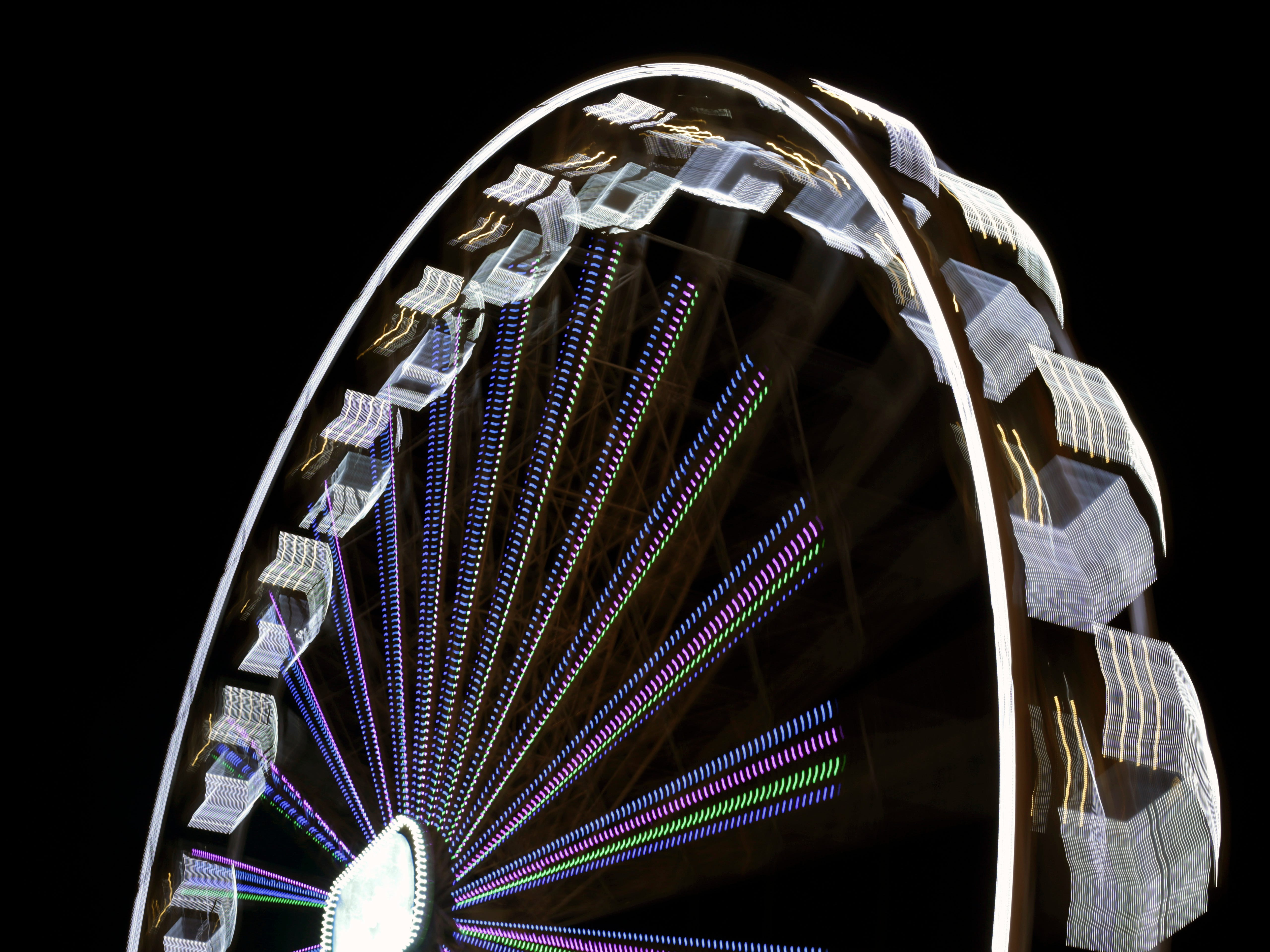 In this picture, taken with a slow shutter speed, a Ferris wheel spins at a Christmas fair in Lisbon, Monday evening, Dec. 3, 2018.