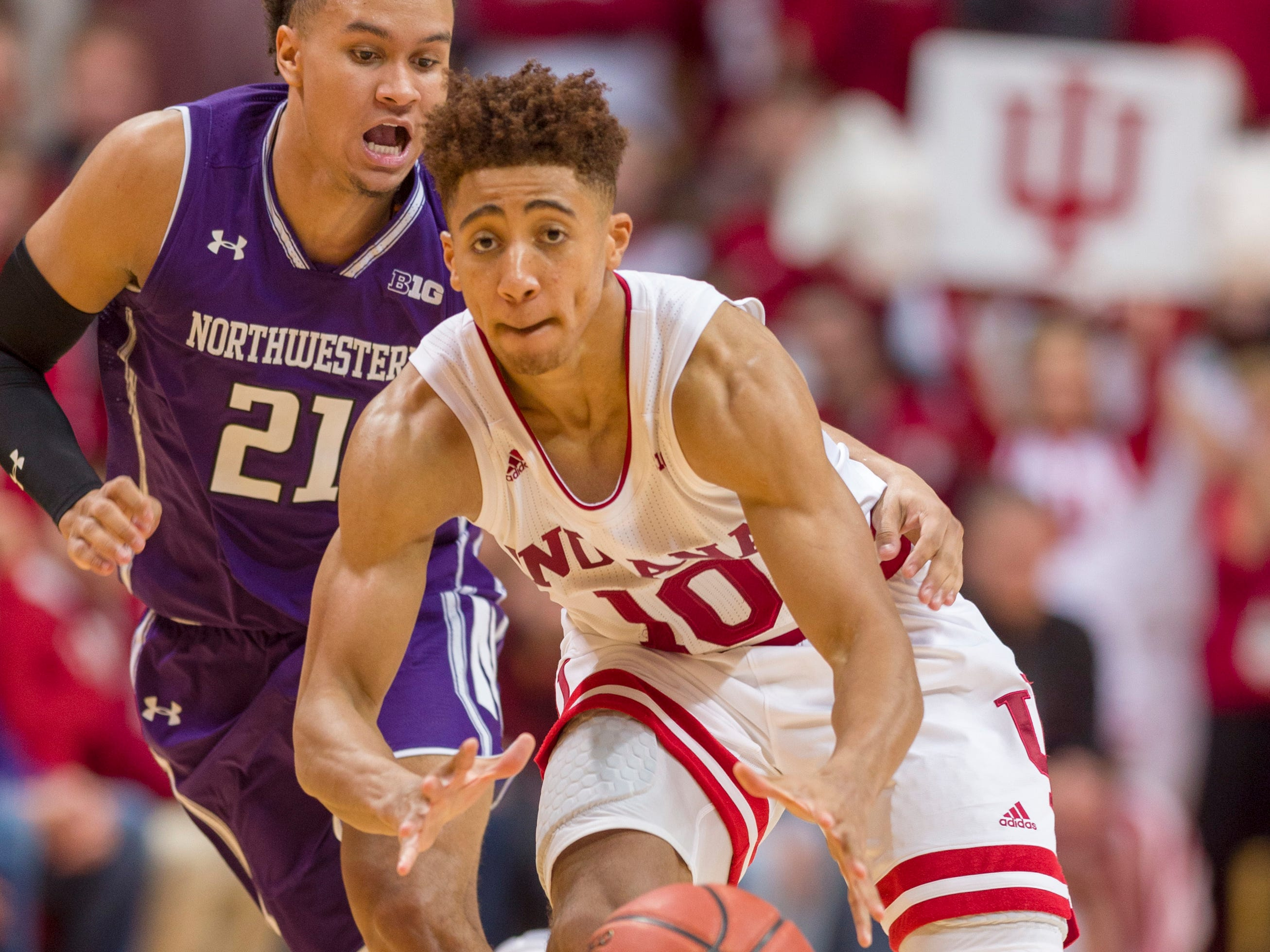 Indiana guard Rob Phinisee (10) makes a pass to a teammate after getting around the defense of Northwestern forward A.J. Turner (21) during the second half of an NCAA college basketball game Saturday, Dec. 1, 2018, in Bloomington, Ind. Indiana won 68-66. (AP Photo/Doug McSchooler)