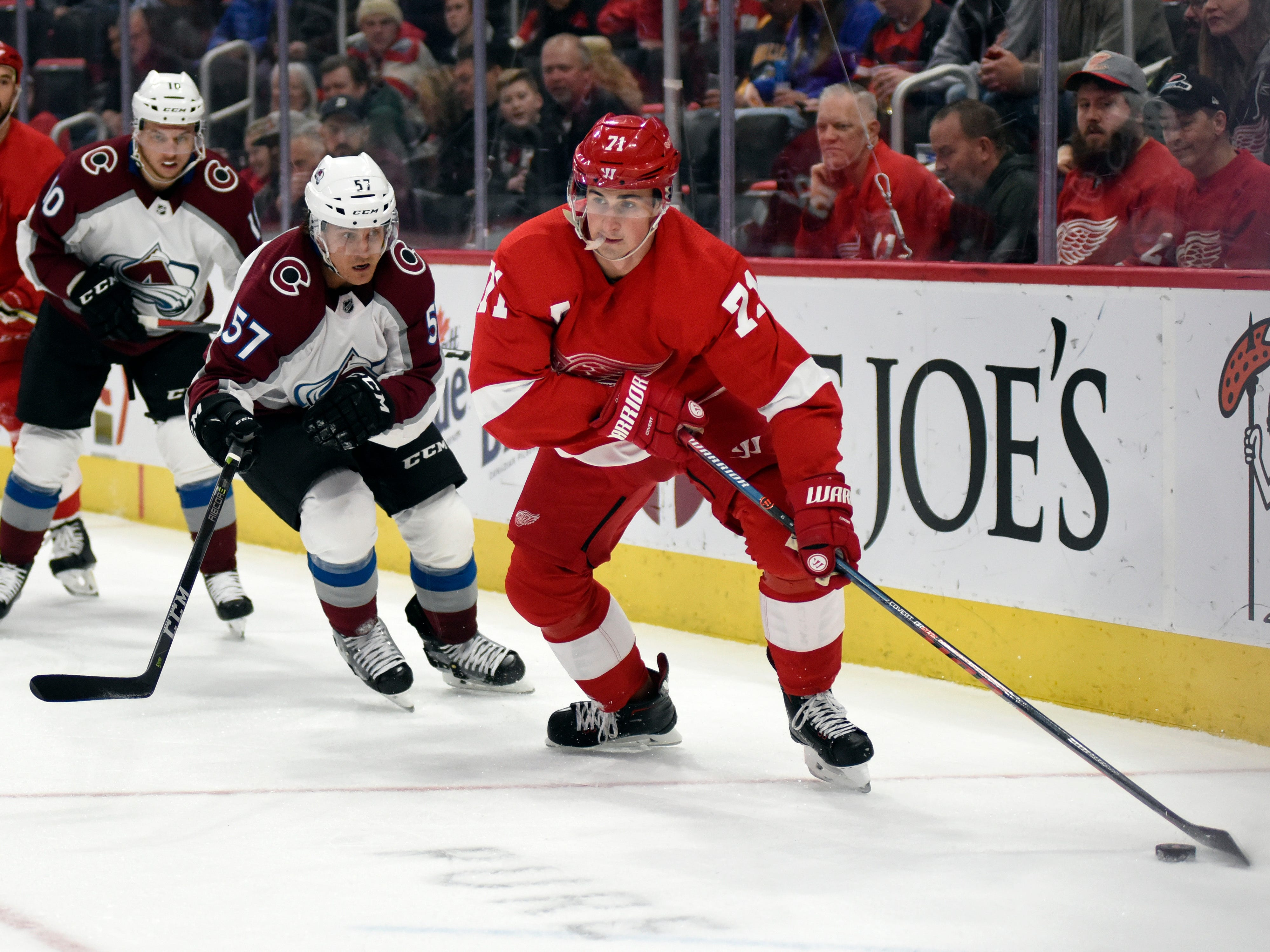 Detroit Red Wings center Dylan Larkin, right, moves the puck away from Colorado Avalanche left wing Gabriel Bourque in the first period of an NHL hockey game in Detroit, Sunday, Dec. 2, 2018.