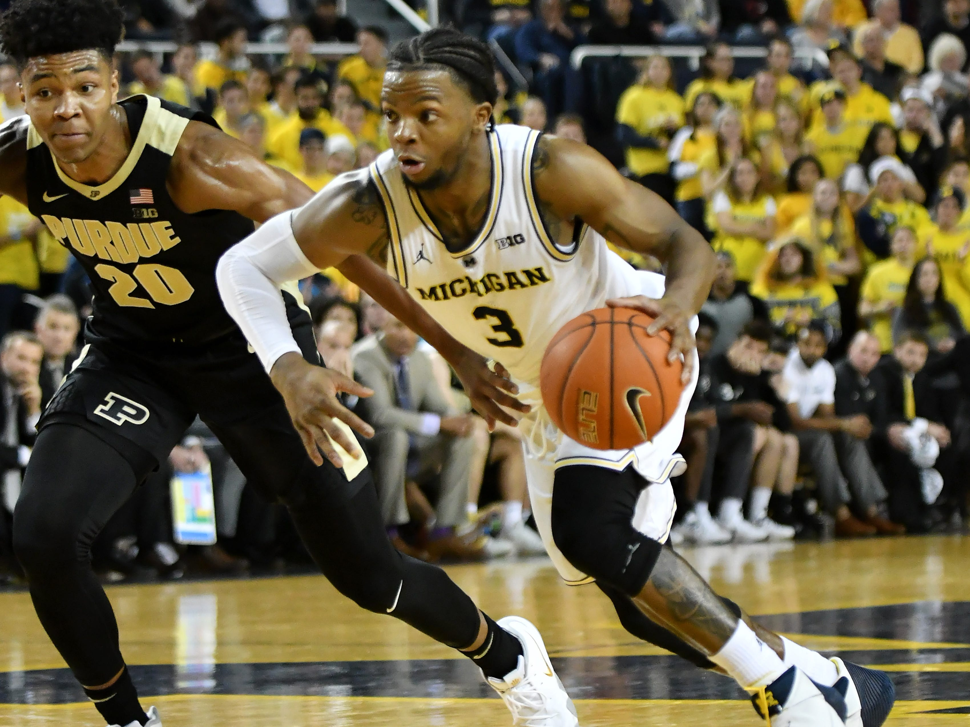 Michigan guard Zavier Simpson (3) pushes alongside Purdue guard Nojel Eastern (20) in the second half.   University of Michigan vs Purdue University at Crisler Arena in Ann Arbor, Mich. on Dec. 1, 2018. Michigan wins, 76-57.