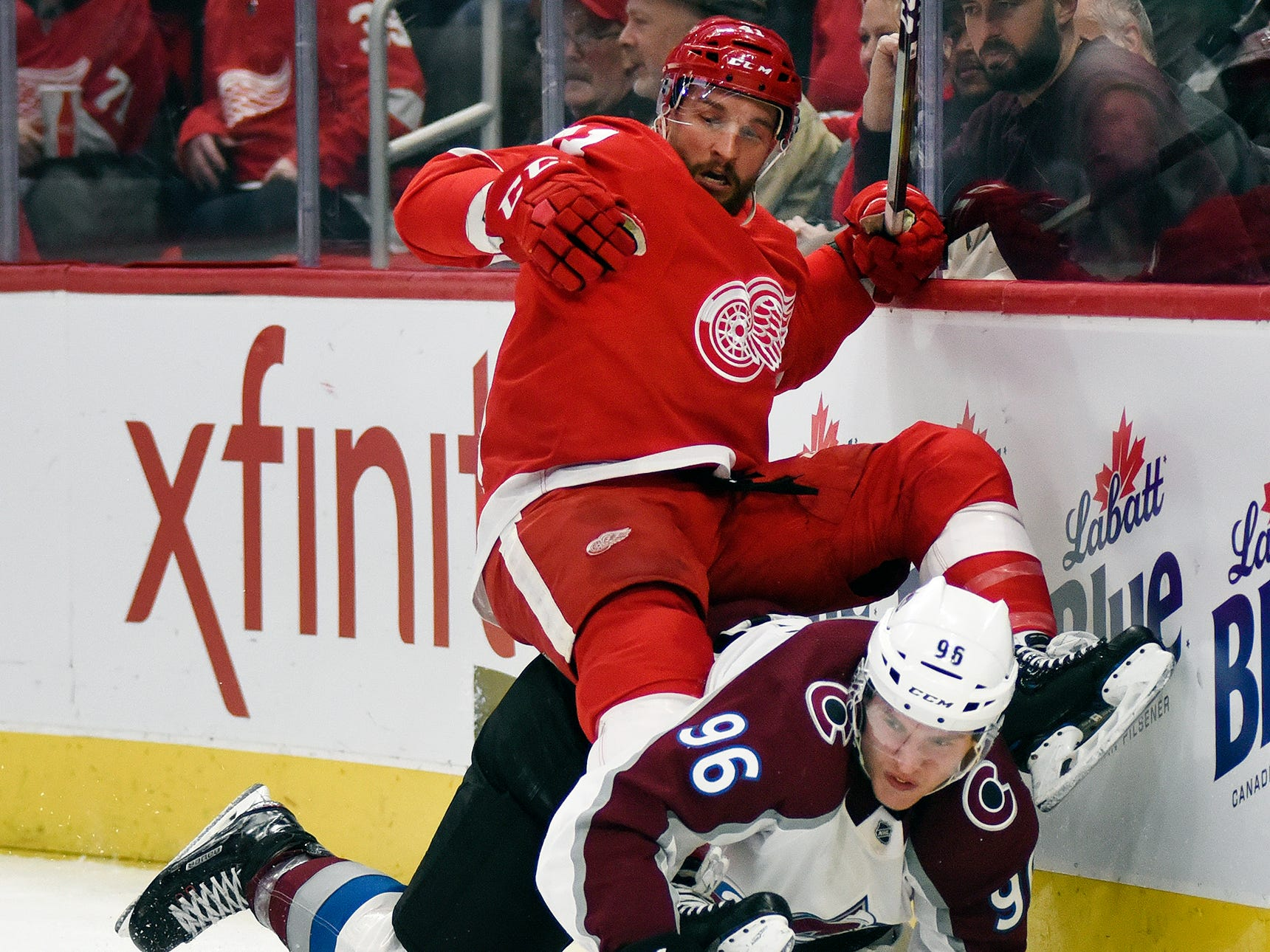 Detroit Red Wings center Luke Glendening, top, falls atop of Colorado Avalanche right wing Mikko Rantanen (96), of Finland, during the first.