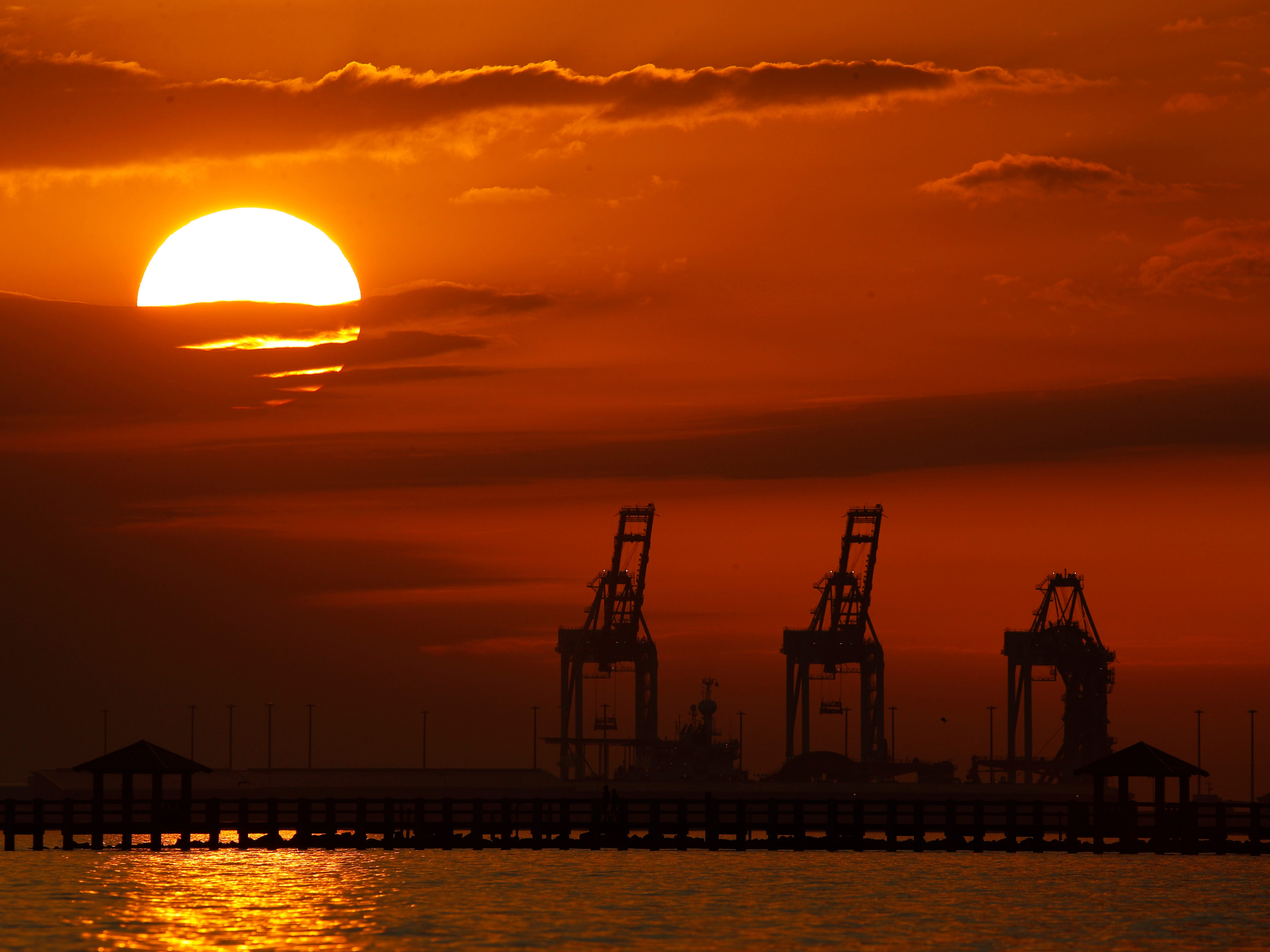 Cranes at the Port of Gulfport are silhouetted by the setting sun Sunday, Dec. 2, 2018, at Gulfport, Miss.