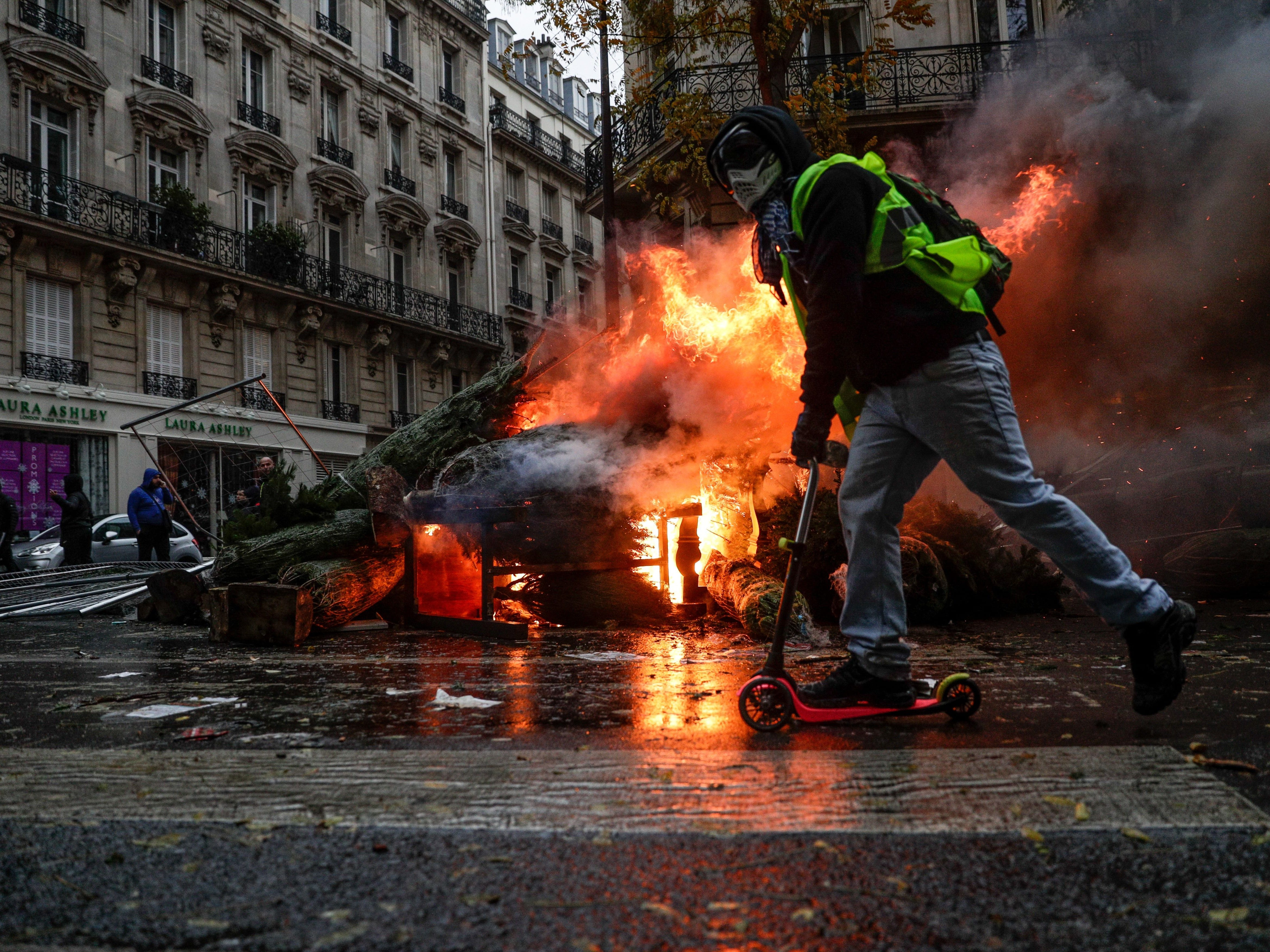TOPSHOT - A demonstrator rides past a fire during a protest of Yellow vests (Gilets jaunes) against rising oil prices and living costs, on December 1, 2018 in Paris. - Speaking at the Paris police's command centre, French Prime Minister said 36,000 people were protesting across France, including 5,500 in the capital for this 3rd nationwide day of blockade ands demos.
