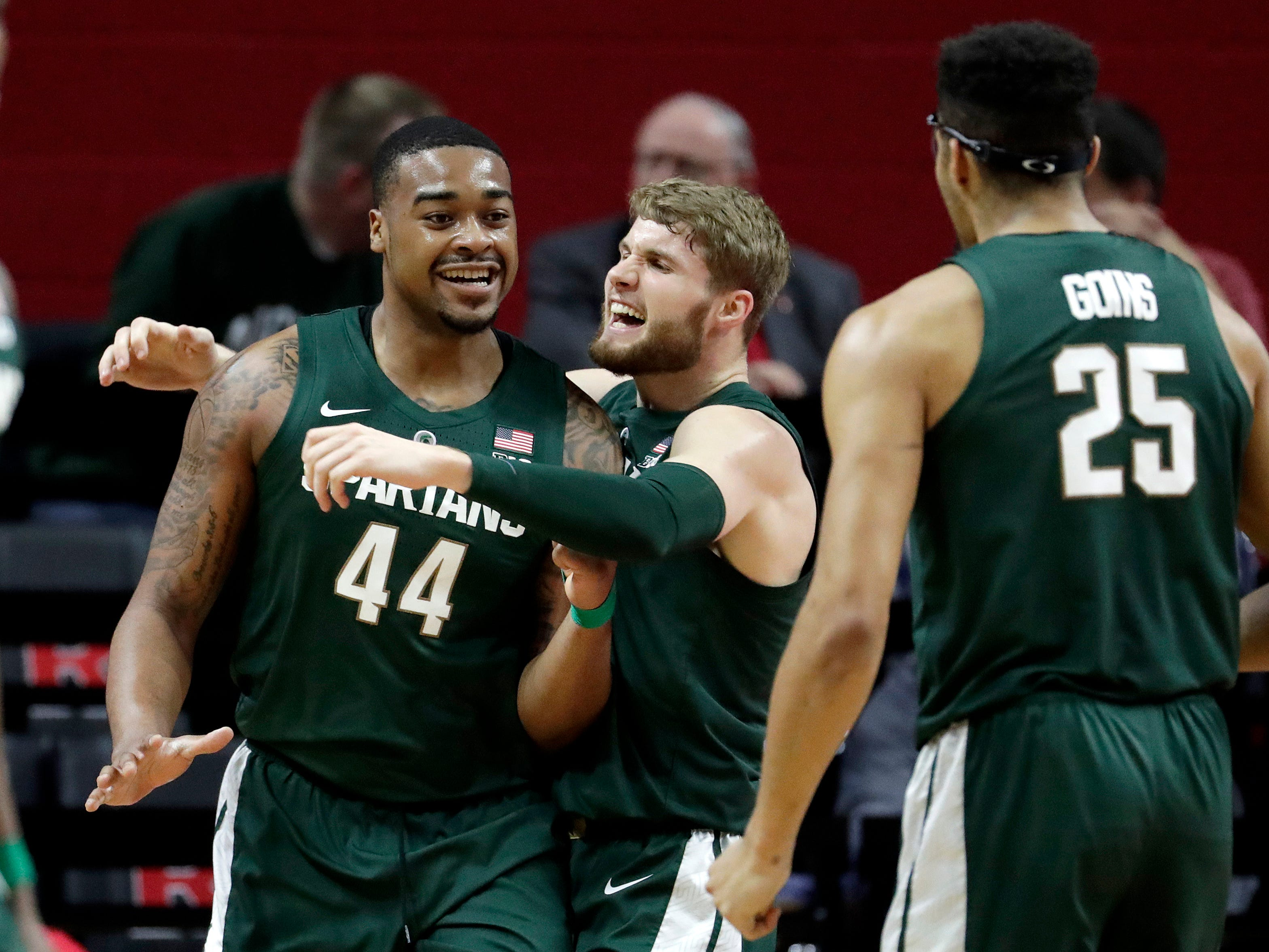 Michigan State forward Nick Ward (44) is hugged by Kyle Ahrens after scoring a basket against Rutgers during the first half of an NCAA college basketball game, Friday, Nov. 30, 2018, in Piscataway, N.J. (AP Photo/Julio Cortez)