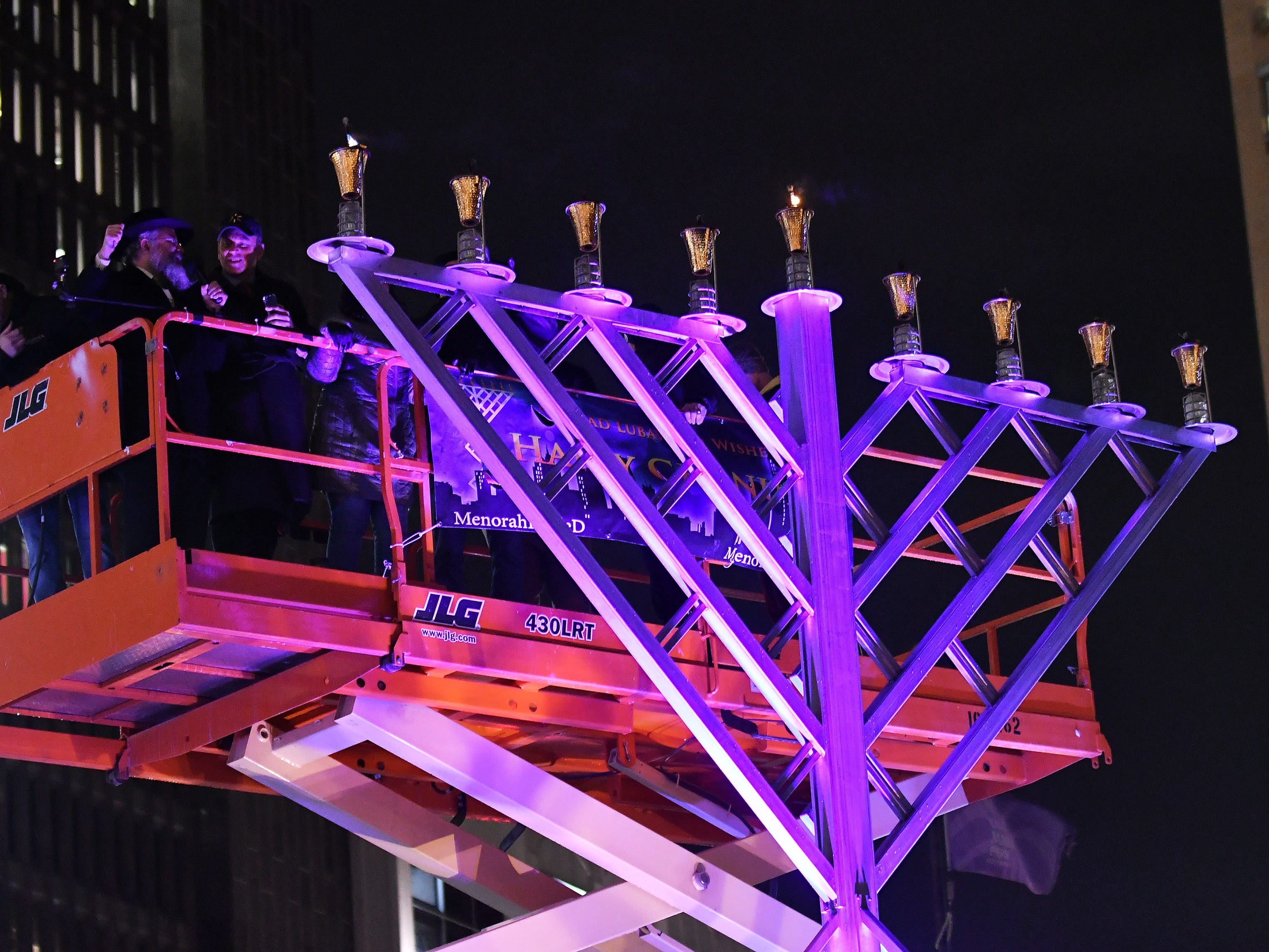 Rabbi Kasriel Shemtov, left, and other officials light the menorah at the Menorah in the D celebration at Campus Martius in Detroit on Dec. 2, 2018.
