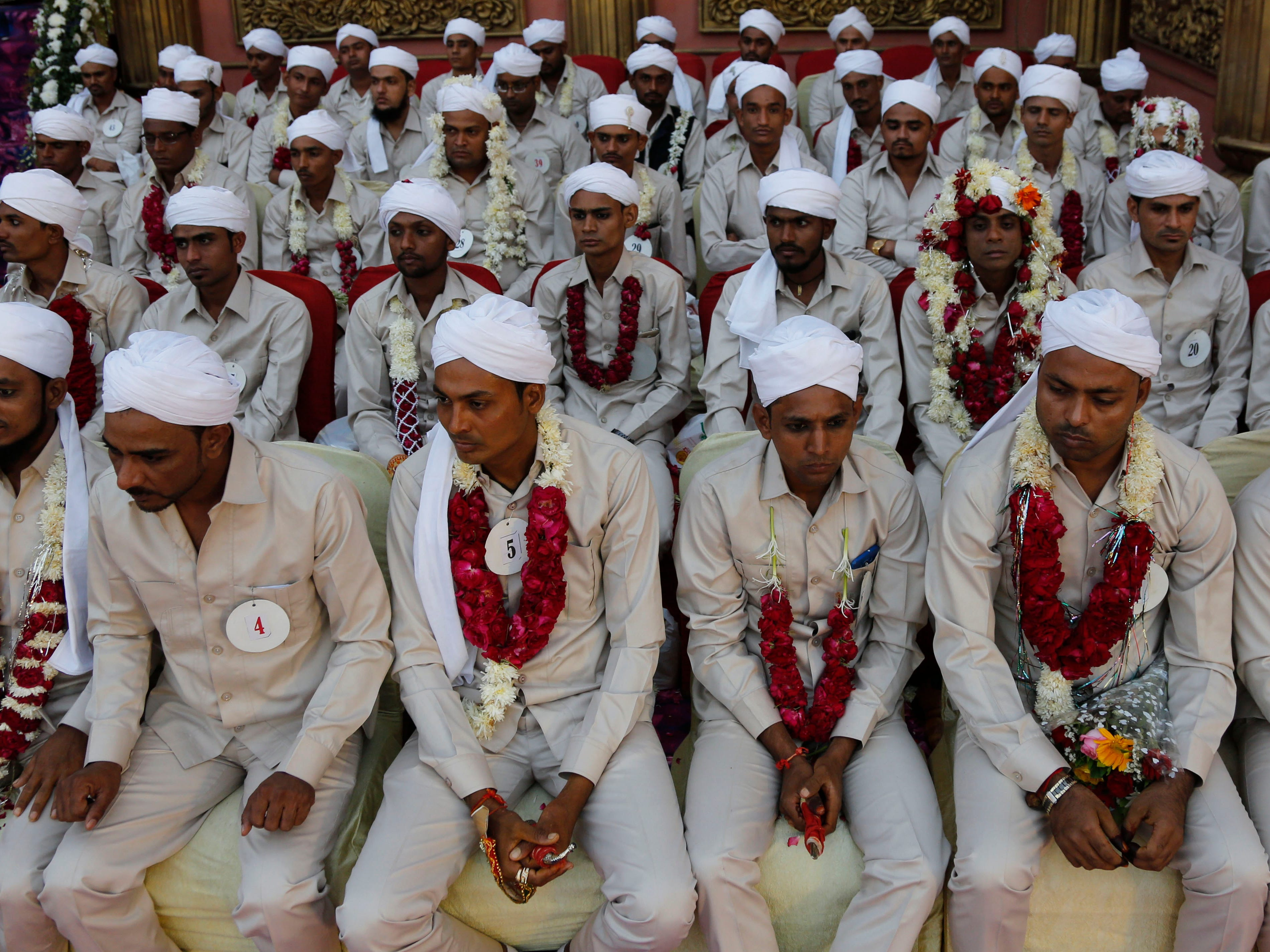 Muslim grooms sit during a mass wedding where 65 couples were married in Ahmadabad, India, Monday, Dec. 3, 2018.
