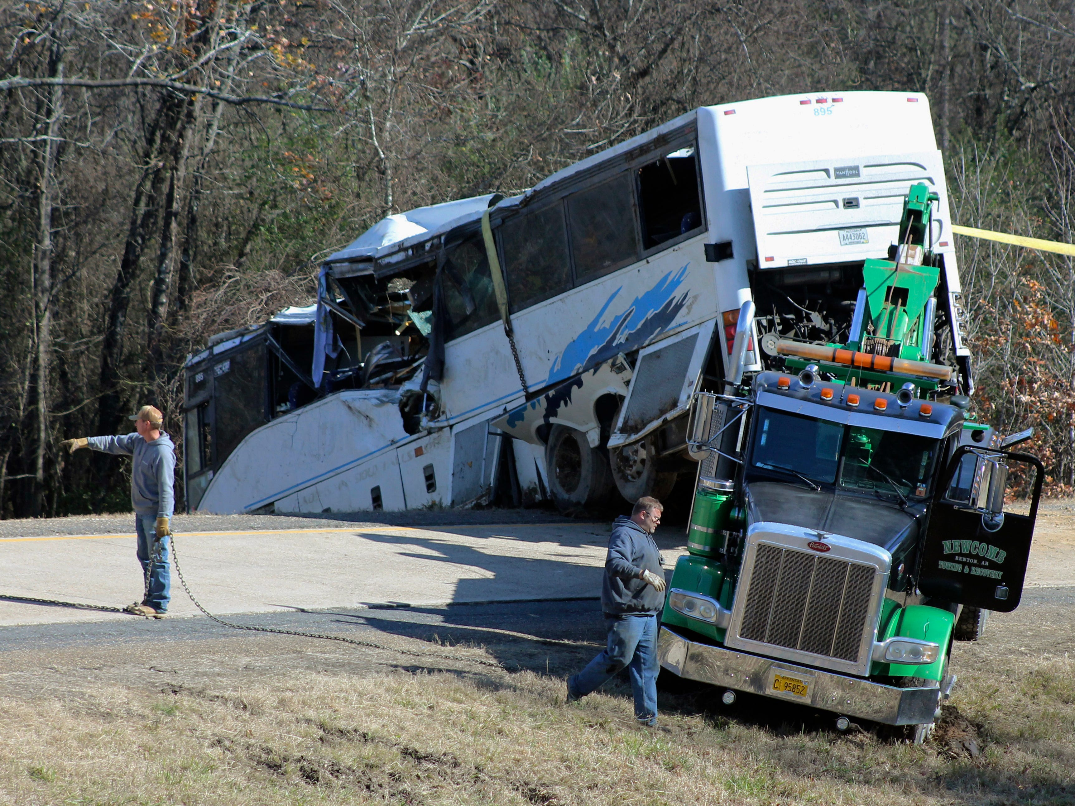 Employees from a wrecker service work to remove a charter bus from a roadside ditch Monday, Dec. 3, 2018, after it crashed alongside Interstate 30 near Benton, Ark. The bus was carrying a youth football team from Tennessee when it rolled off an interstate off-ramp and overturned before sunrise Monday. The elementary-school age football team from Orange Mound Youth Association in southeast Memphis had played in a tournament in Dallas over the weekend.
