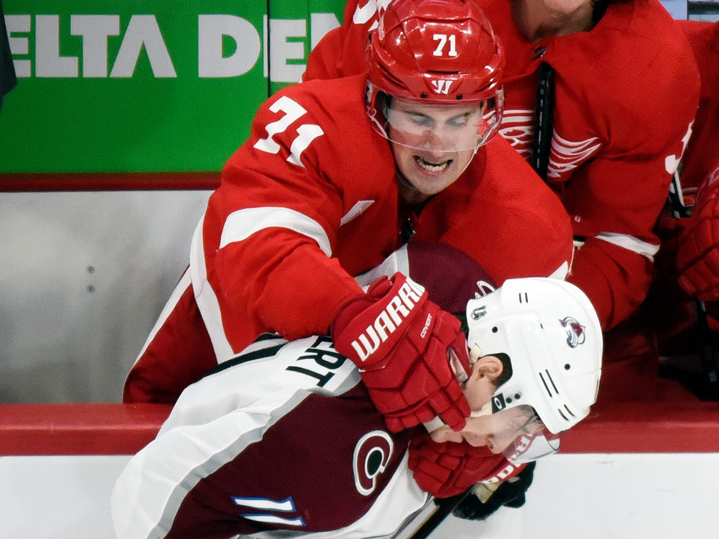 Detroit Red Wings' Dylan Larkin (71) grabs Colorado Avalanche left wing Matt Calvert (11) during the third period.