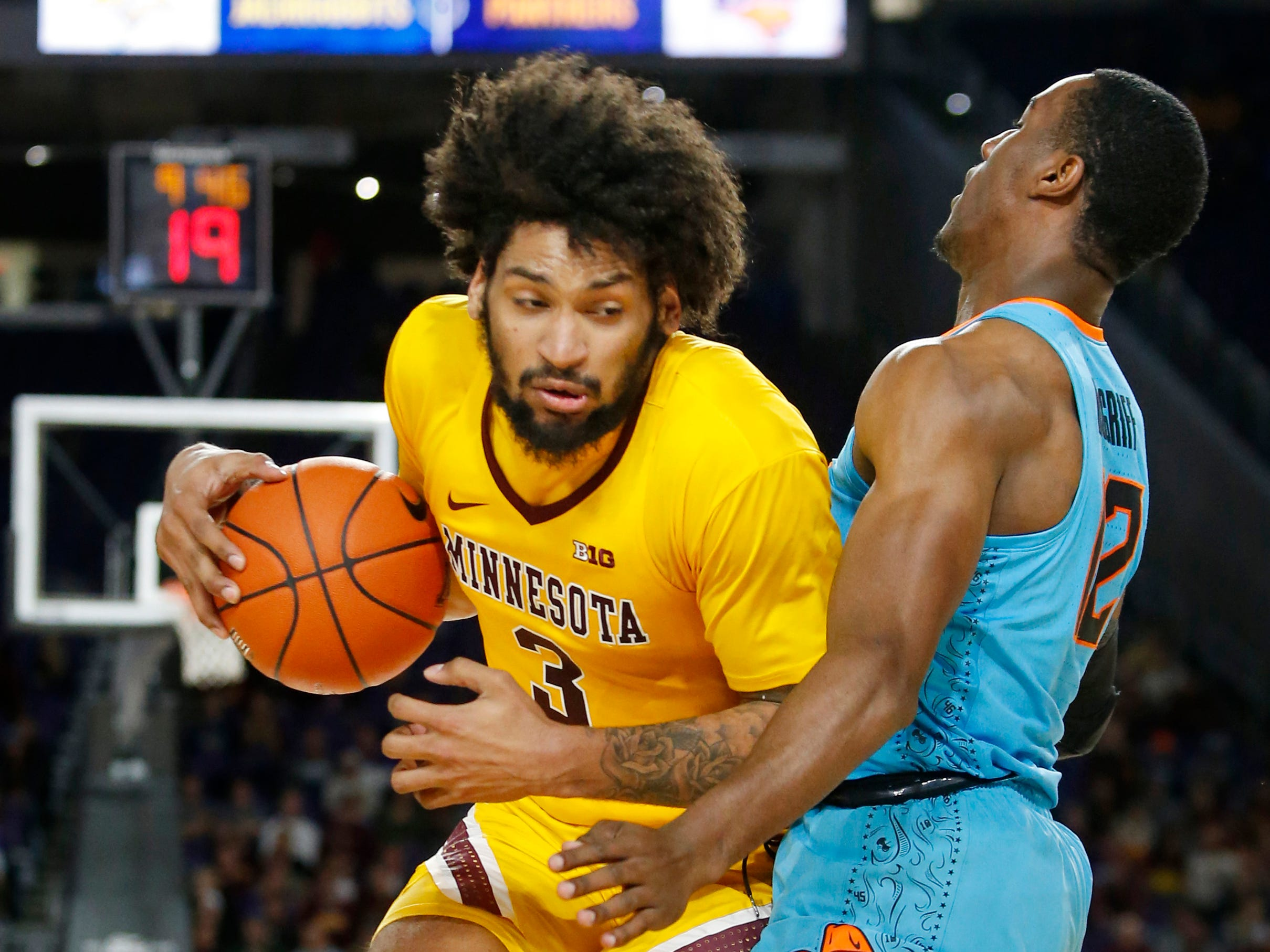 Minnesota's Jordan Murphy (3) drives around Oklahoma State's Cameron McGriff during the first half of an NCAA college basketball game Friday, Nov. 30, 2018, in Minneapolis. (AP Photo/Bruce Kluckhohn)