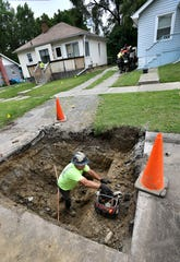A worker from Lang Construction wrenches fittings in place for new copper pipe as they replace water lines on Arlene St. in Flint on, June 20, 2018.