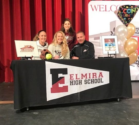 Elmira Express senior Bella Reese, second from left, signs to play softball at St. Bonaventure University during a ceremony Nov. 19 at Elmira High School. Next to her are her parents, Dain and Courtney Reese, and behind them is Express coach Becca Saggiomo.