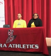 Elmira Express senior Roosevelt (Alex) Simmons signs to play lacrosse at the College of St. Rose during a ceremony Nov. 19 at Elmira High School. Also pictured is his mom, Shari Simmons.