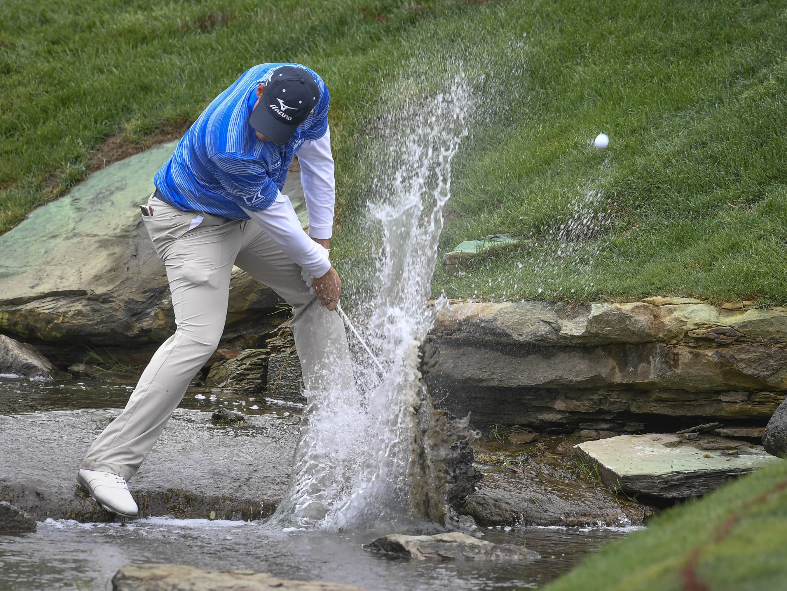 Adam Schenk, of Vincennes, Indiana, hits a chip shot out of the creek on No. 16 as players try to finish the second round of the United Leasing & Finance Championship golf tournament at Victoria National Golf Club on Saturday, April 22, 2017.
