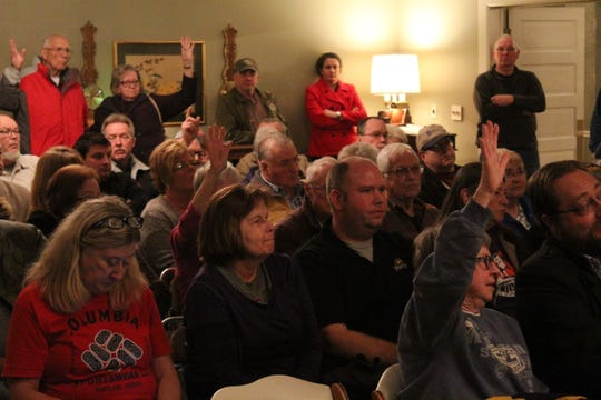 Plot owners, including Becky White,  far right, raise their hands to vote yes to give up ownership of Oakwood Cemetery to Ballville Township. The proposal was defeated by a 20-to-16 vote.