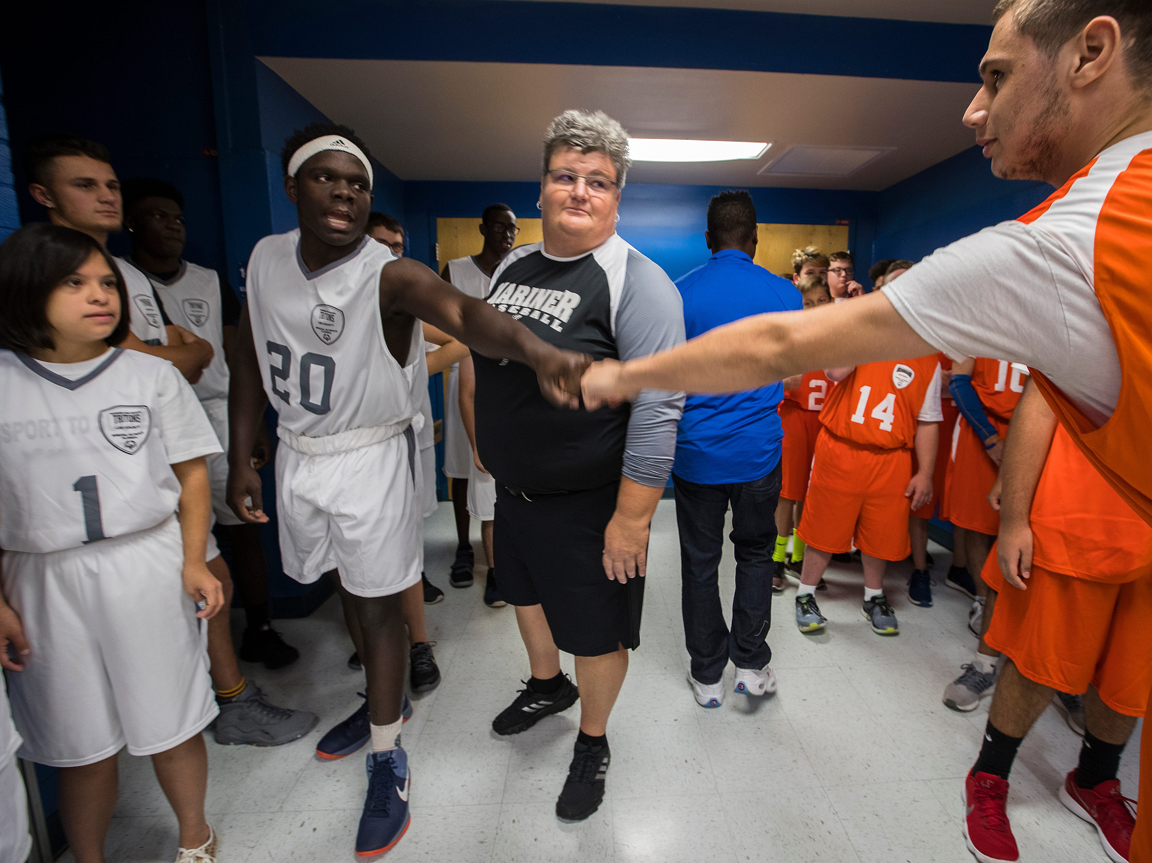 Mariner's Victor Wright, left, and Cape Coral's Luis Duran, pump fists prior to their game Friday morning, November 16, 2018. Cape Coral High hosted Mariner during a Unified sports basketball game at Friday, November 16, 2018. Lee County schools have significantly expanded the size, reach and potential impact of its Special Olympics commitment this year with the addition of what is known as Unified sports, in which students with and without disabilities work together on organized teams for a season. A number of Lee County high schools are participating this first year and are playing already in basketball, one of four high school Special Olympics sports. Track and field will be held in the spring. Flag football and soccer will be added in the future and reach the middle school level. The goal: greater participation, inclusion and understanding.