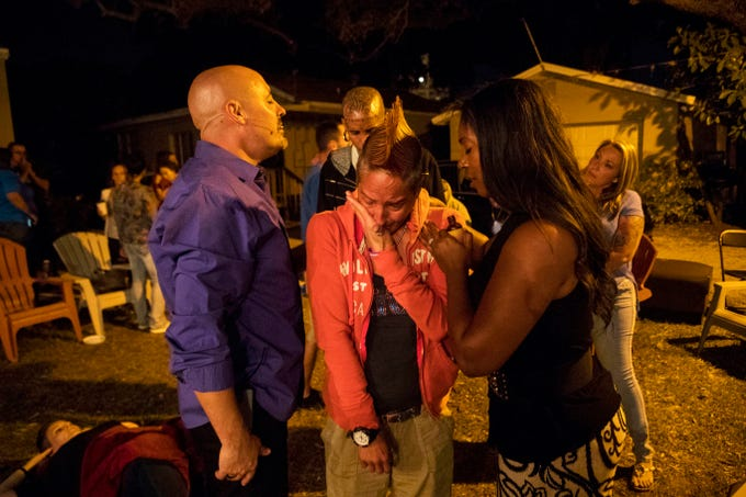 """Kathy Hitt is prayed over by Pastor Craig Hunt and Sheanna Hunt during a Light Xplosion Ministry service at Recovering Lives sober home in Fort Myers on 11/3/2018. Hitt is a resident at the sober home. She was addicted to meth. She said """"20 years are gone, I'm fighting for my life."""" One the left is resident, Amber Boley and on the right is resident, Amber Kovach."""