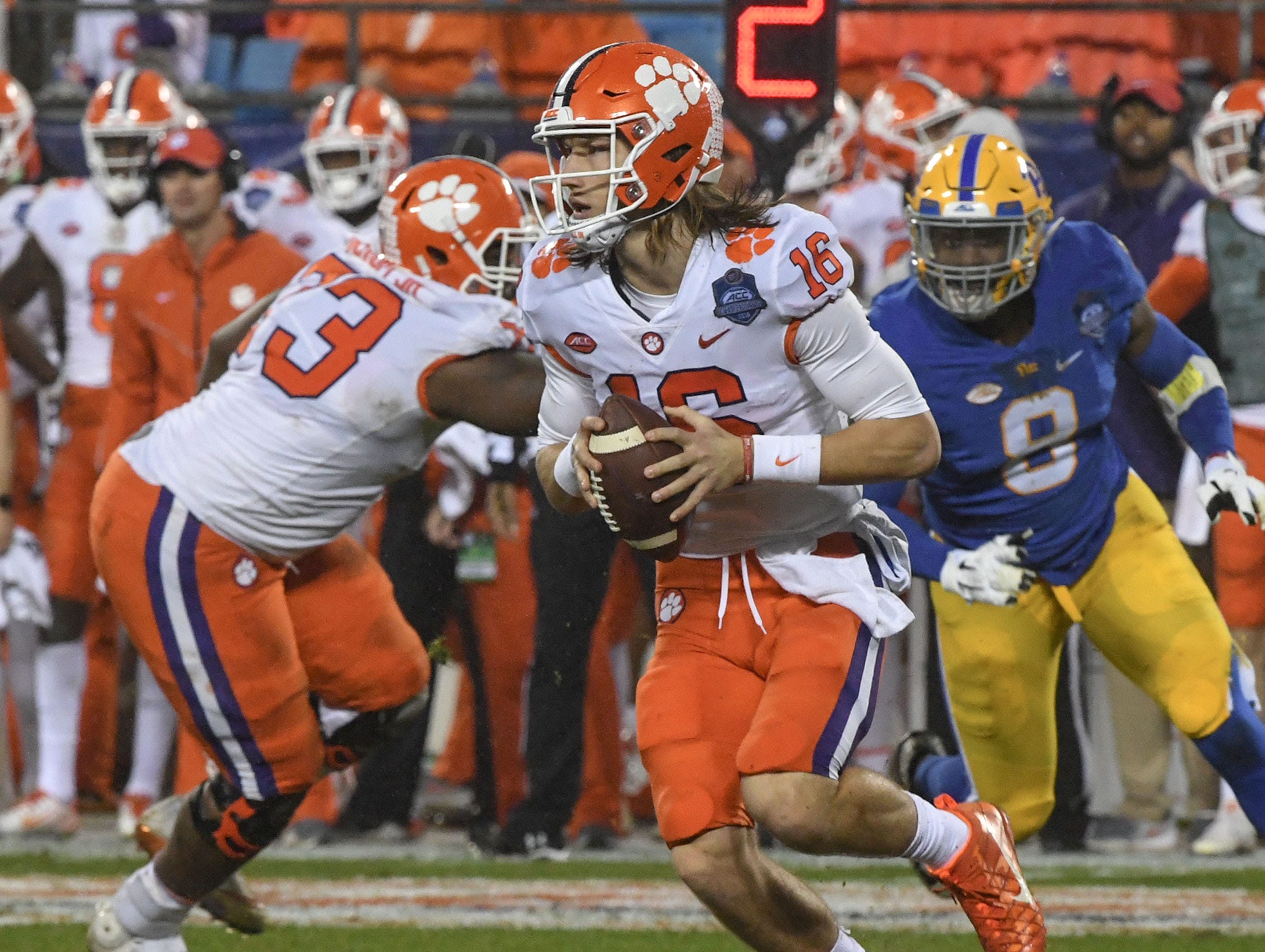 Clemson quarterback Trevor Lawrence (16) rolls out to pass near Pittsburgh linebacker Saleem Brightwell(9) during the second quarter of the Dr. Pepper ACC football championship at Bank of America Stadium in Charlotte, N.C. on Saturday, December 1, 2018.