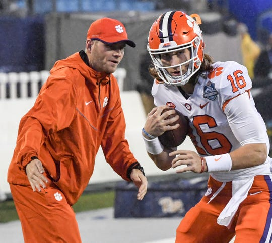 Clemson quarterback coach Brandon Streeter, left, warm ups with Clemson quarterback Trevor Lawrence (16) before the game of the Dr. Pepper ACC football championship at Bank of America Stadium in Charlotte, N.C. on Saturday, December 1, 2018.