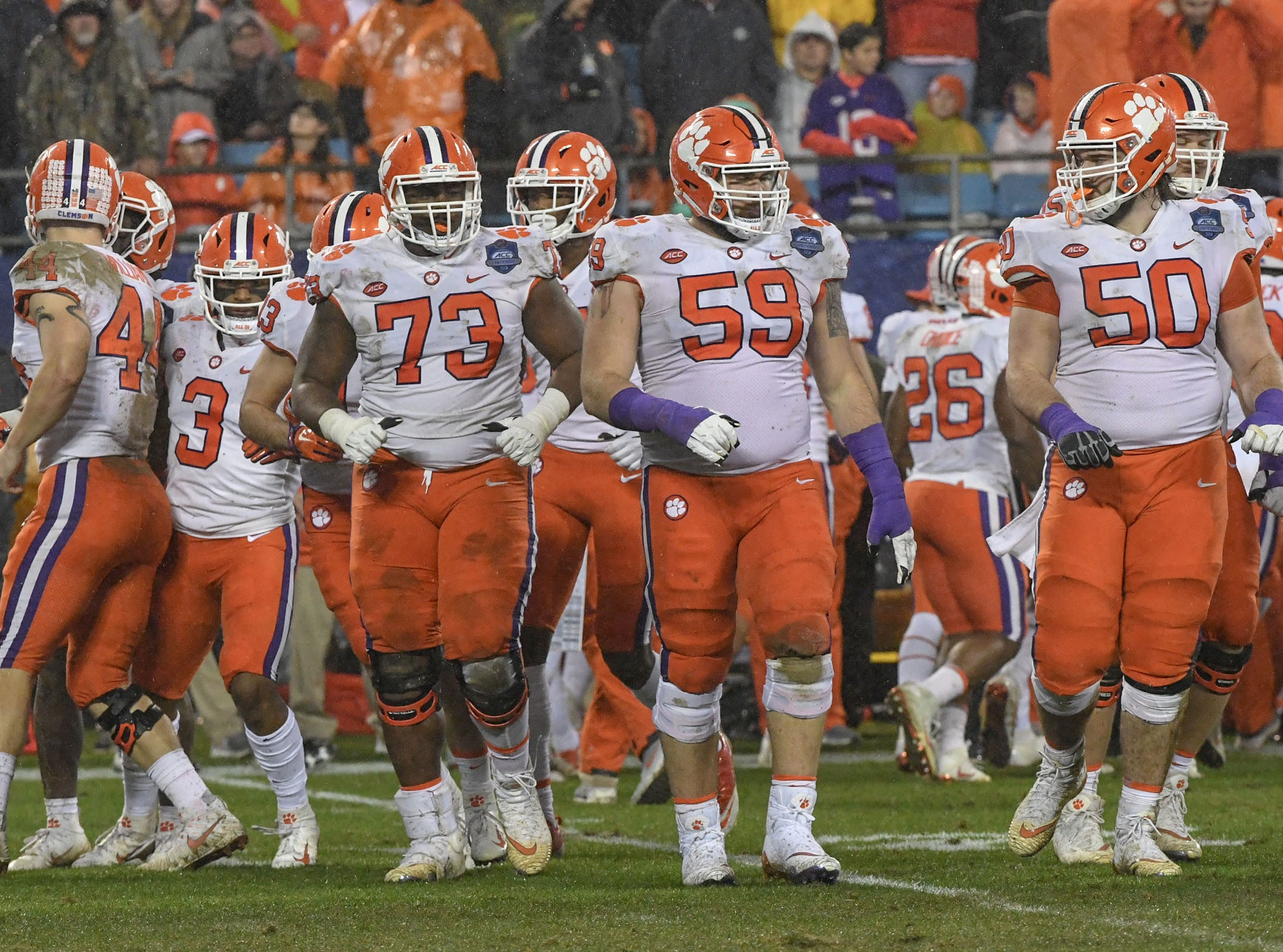 Clemson quarterback Trevor Lawrence (16), left, and offensive linemen walk up for a play during the third quarter of the Dr. Pepper ACC football championship at Bank of America Stadium in Charlotte, N.C. on Saturday, December 1, 2018.