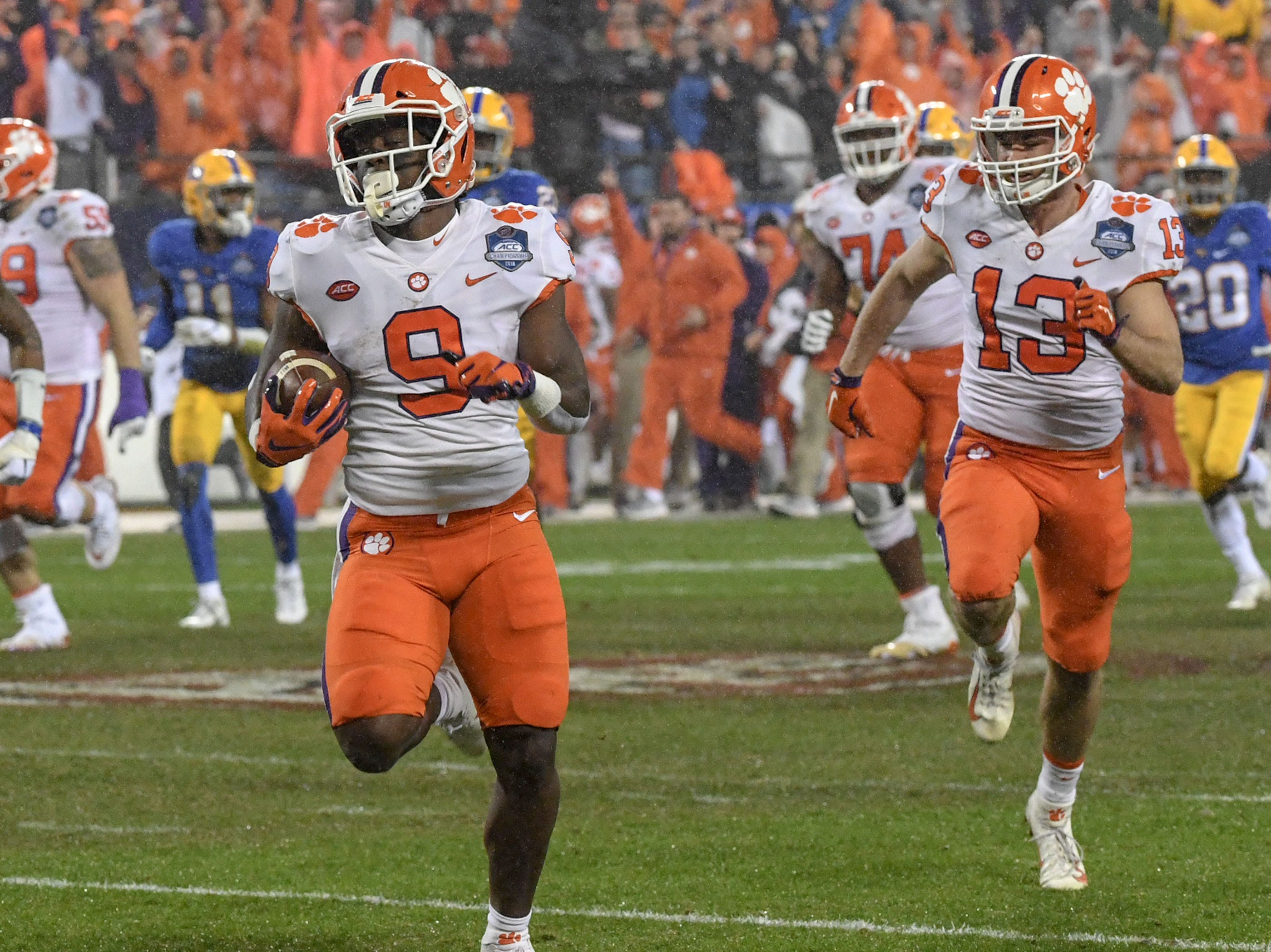 Clemson running back Travis Etienne (9) runs the first play from scrimmage 75 yards for a touchdown with wide receiver Hunter Renfrow (13) nearby, against Pitt during the first quarter of the Dr. Pepper ACC football championship at Bank of America Stadium in Charlotte, N.C. on Saturday, December 1, 2018.