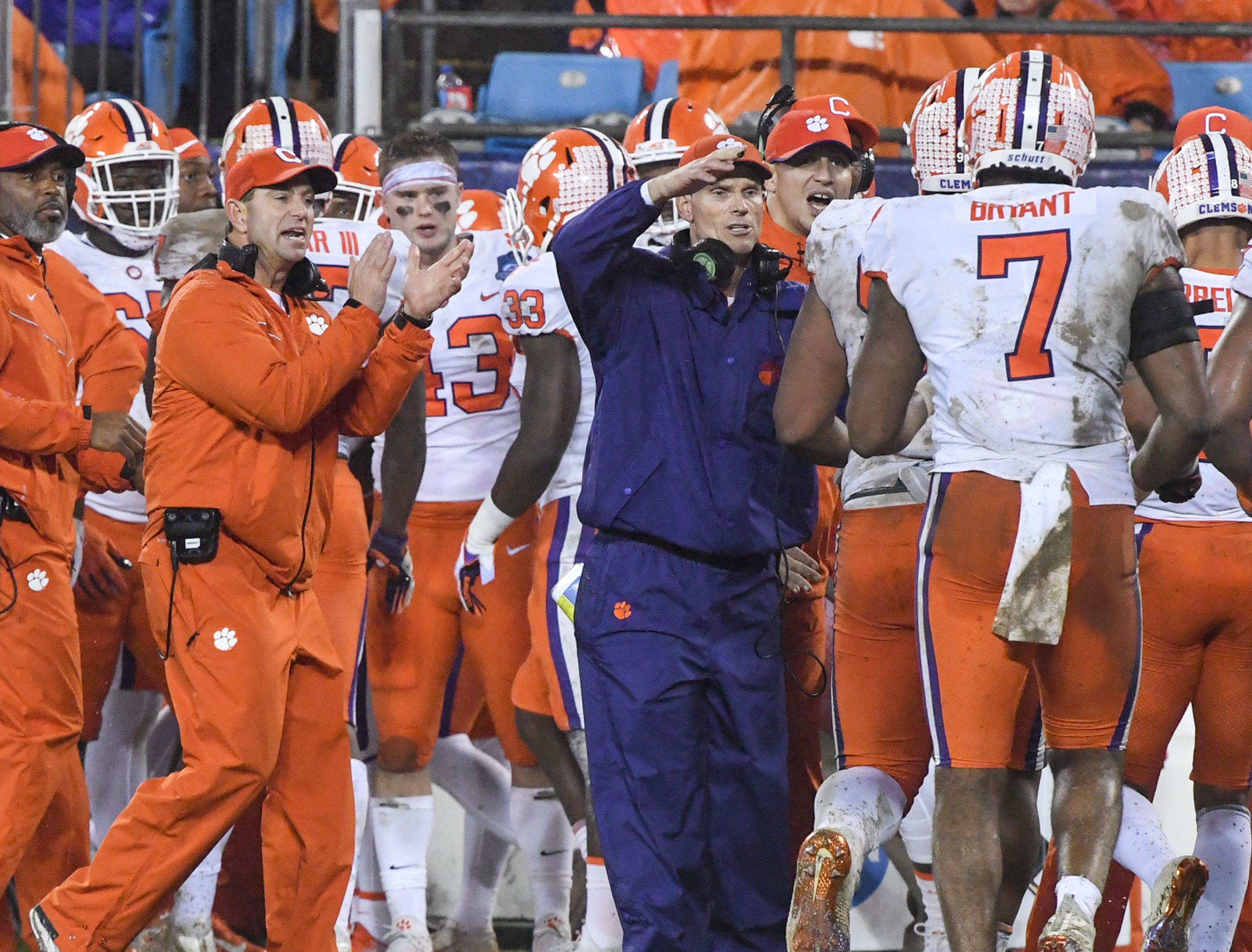 Clemson Head Coach Dabo Swinney, left, and Clemson Defensive Coordinator Brent Venables greet defensive lineman Austin Bryant (7) and others after stopping Pittsburgh offense during the third quarter of the Dr. Pepper ACC football championship at Bank of America Stadium in Charlotte, N.C. on Saturday, December 1, 2018.