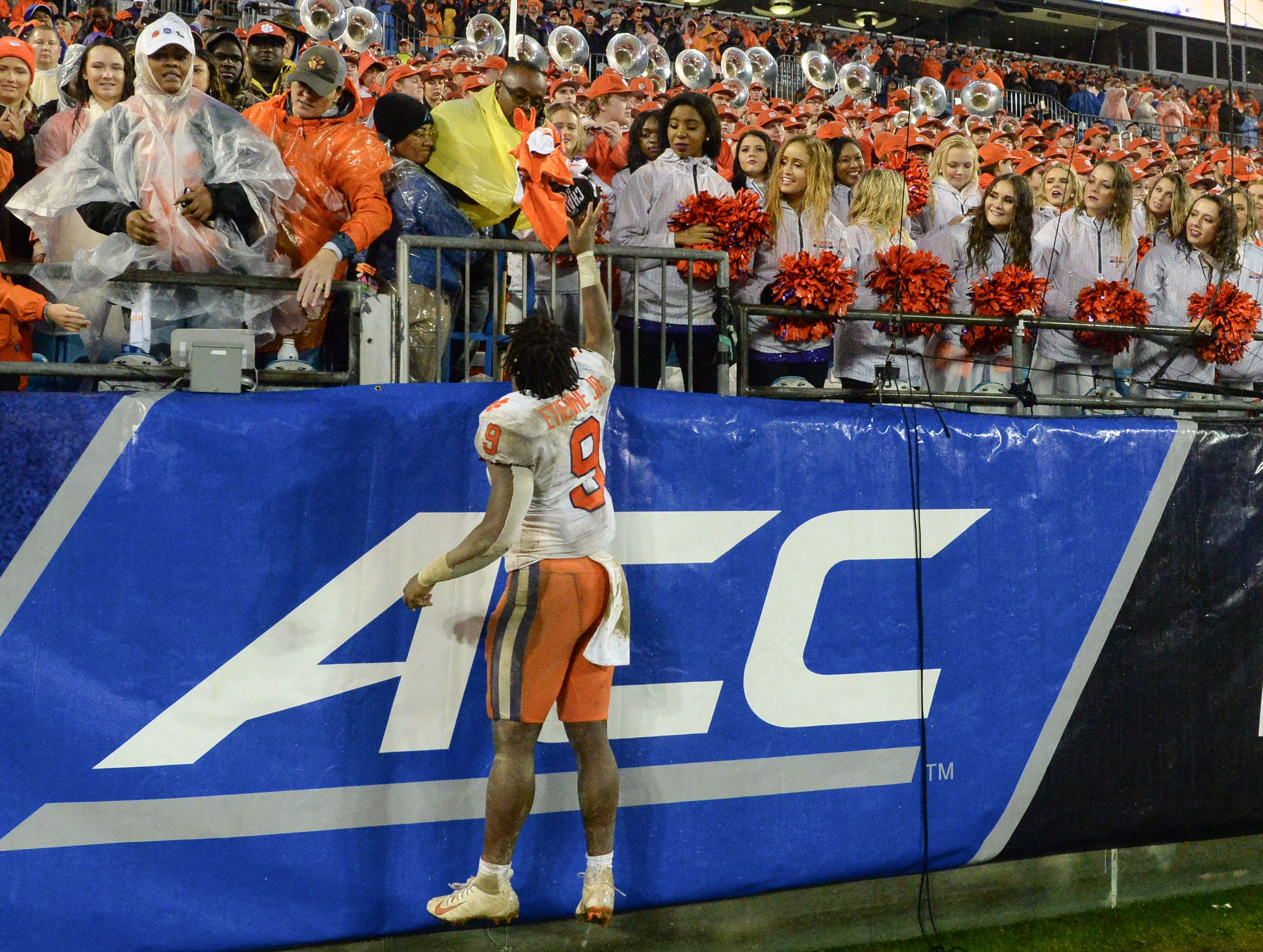 Clemson running back Travis Etienne (9) jumps up with fans after the game at the Dr. Pepper ACC football championship at Bank of America Stadium in Charlotte, N.C. on Saturday, December 1, 2018.