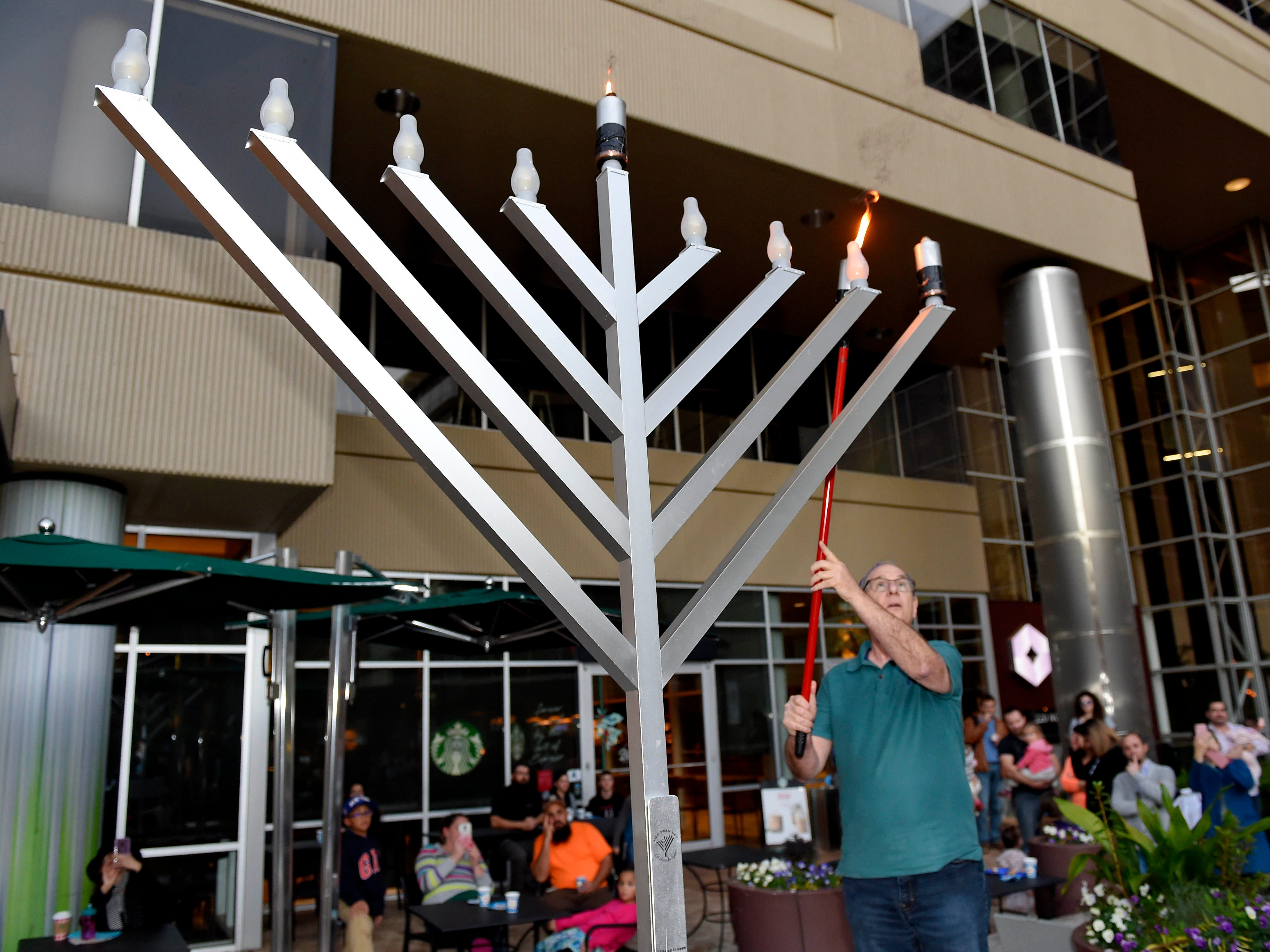 Dr. Michael Wolff lights the menorah. The annual Jewish celebration of Chanukah was kicked off with the lighting of the Menorah at NOMA Square Sunday, Dec. 2, 2018.