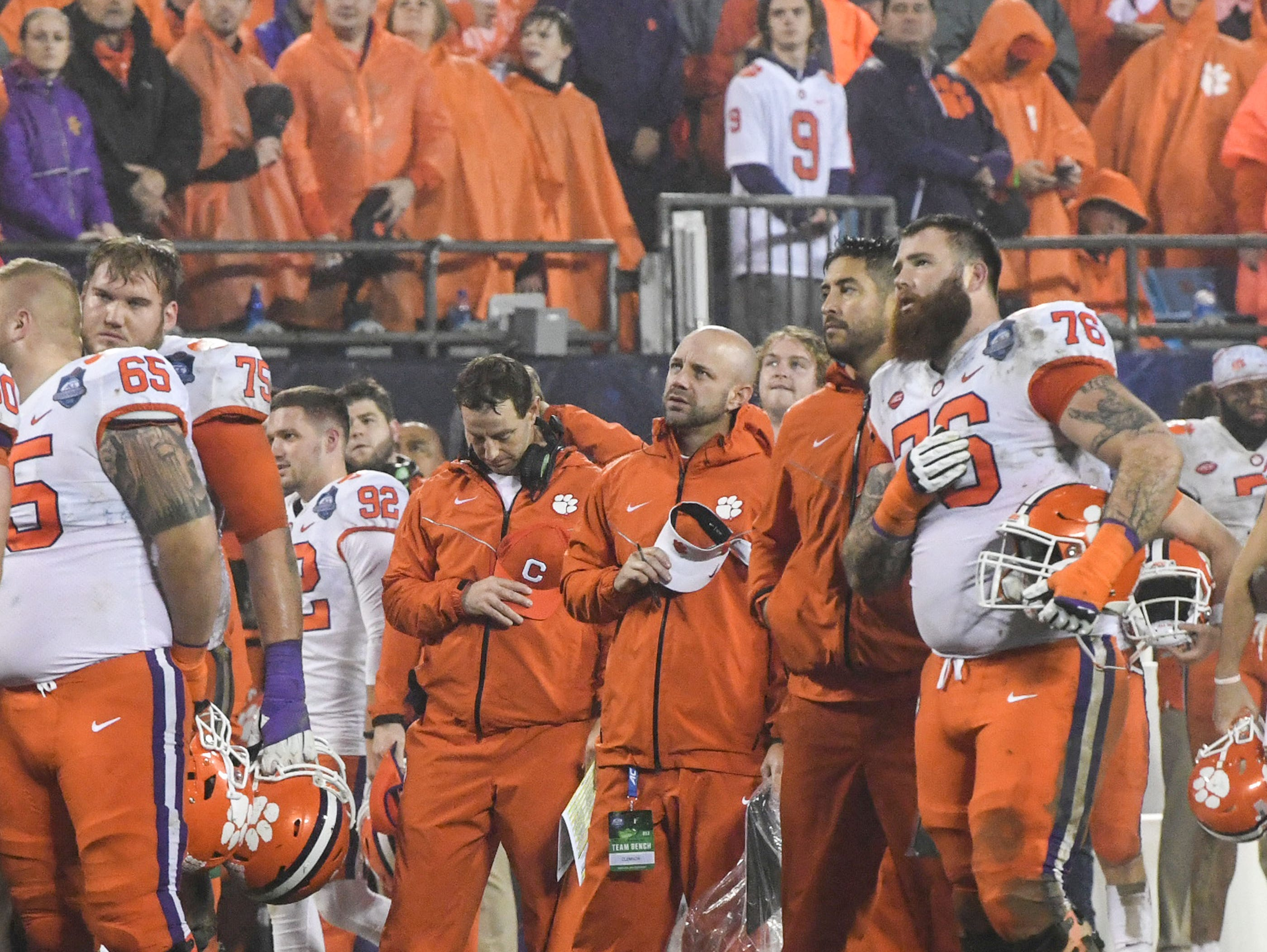 "Clemson Head Coach Dabo Swinney, middle, offensive lineman Sean Pollard (76), players and fans stop to hear a man sing ""God Bless America"" during a break in play, during the third quarter of the Dr. Pepper ACC football championship at Bank of America Stadium in Charlotte, N.C. on Saturday, December 1, 2018."