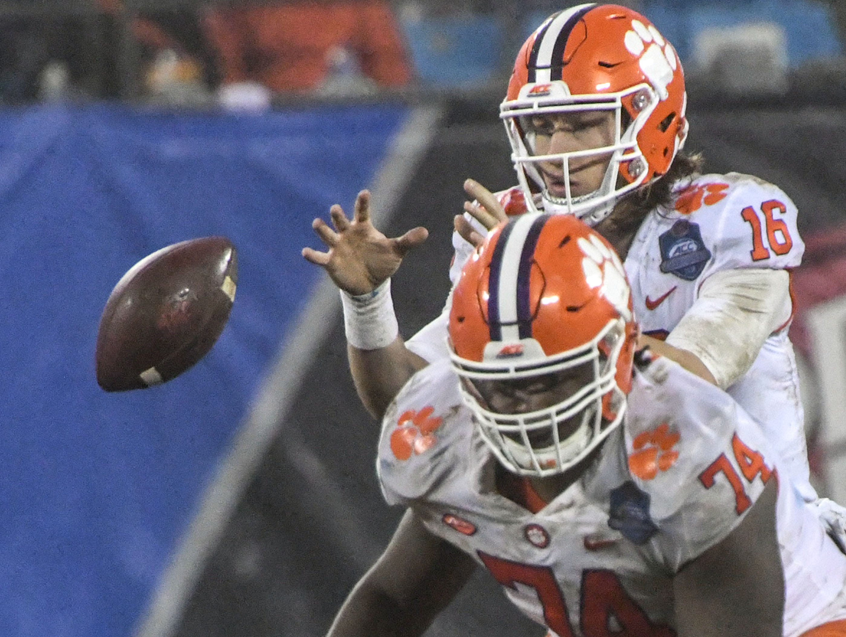 Clemson quarterback Trevor Lawrence (16) takes a snap near offensive guard John Simpson (74) during the second quarter of the Dr. Pepper ACC football championship at Bank of America Stadium in Charlotte, N.C. on Saturday, December 1, 2018.
