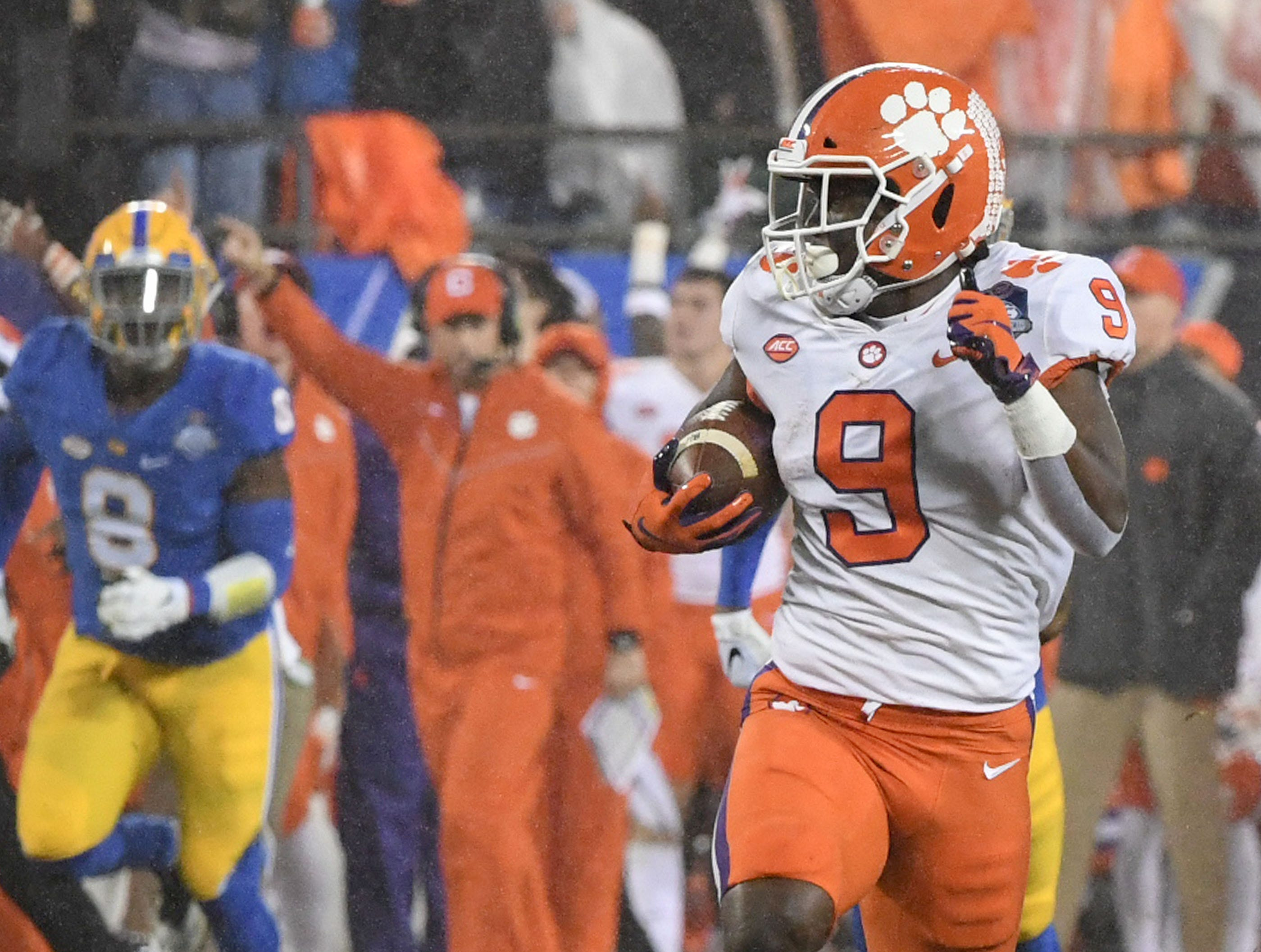 Clemson running back Travis Etienne (9) runs the first play from scrimmage 75 yards for a touchdown as Clemson Head Coach Dabo Swinney raises his arm in the background, against Pitt during the first quarter of the Dr. Pepper ACC football championship at Bank of America Stadium in Charlotte, N.C. on Saturday, December 1, 2018.