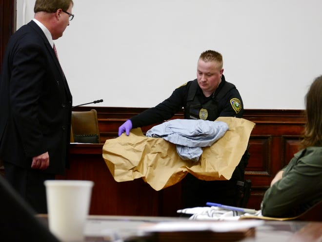 John Marshall, an officer with the Great Falls Police Department, shows jurors stained bedclothes collected at the scene of the alleged rape during Monday's trial of Richard Lee Tome.